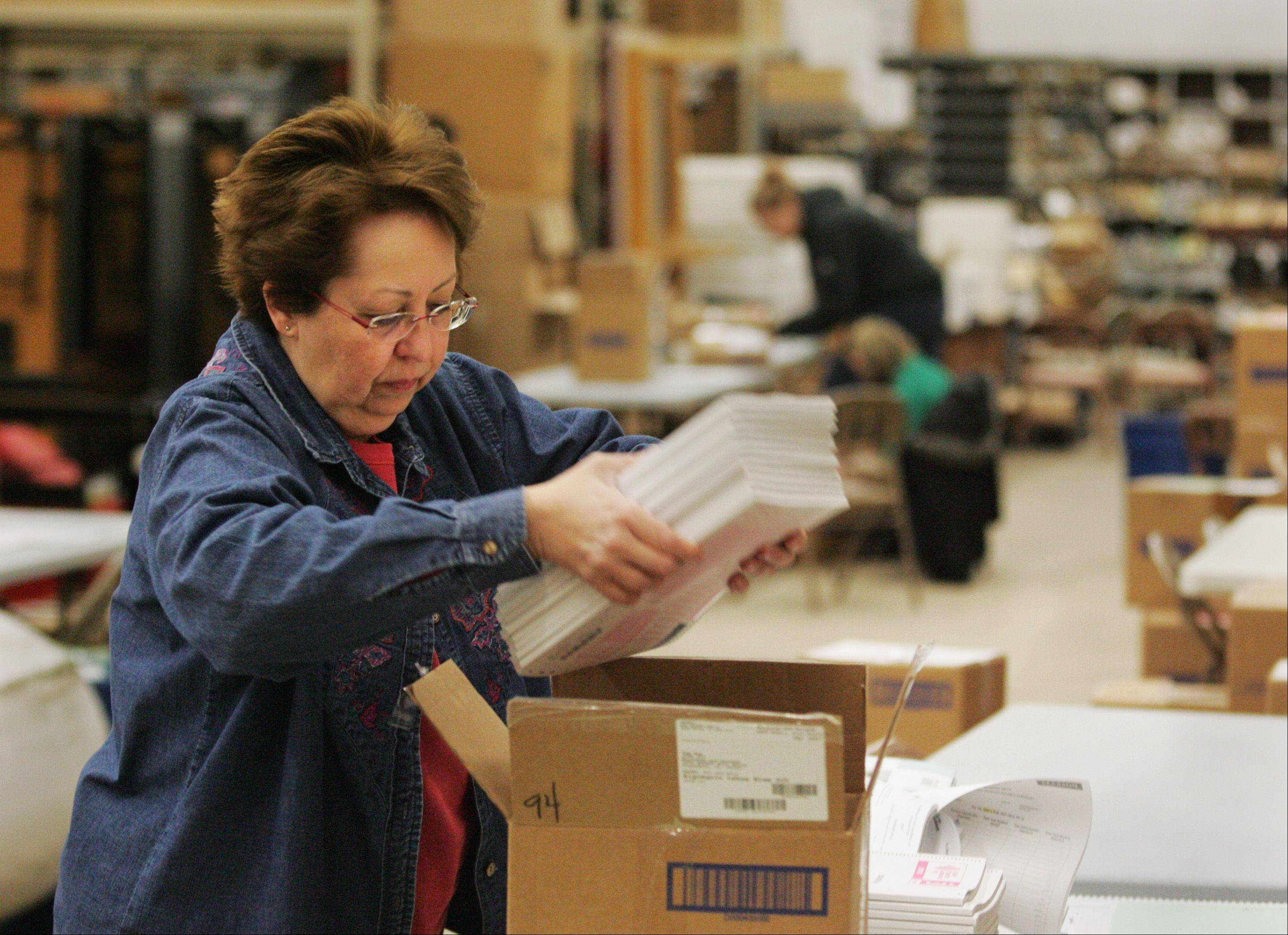 Community Unit District 300 director of transportation Donna Bordsen places a stack of ISAT booklets into a box at the district transportation center in Algonquin. Testing finished March 15. Scores will be released next fall.