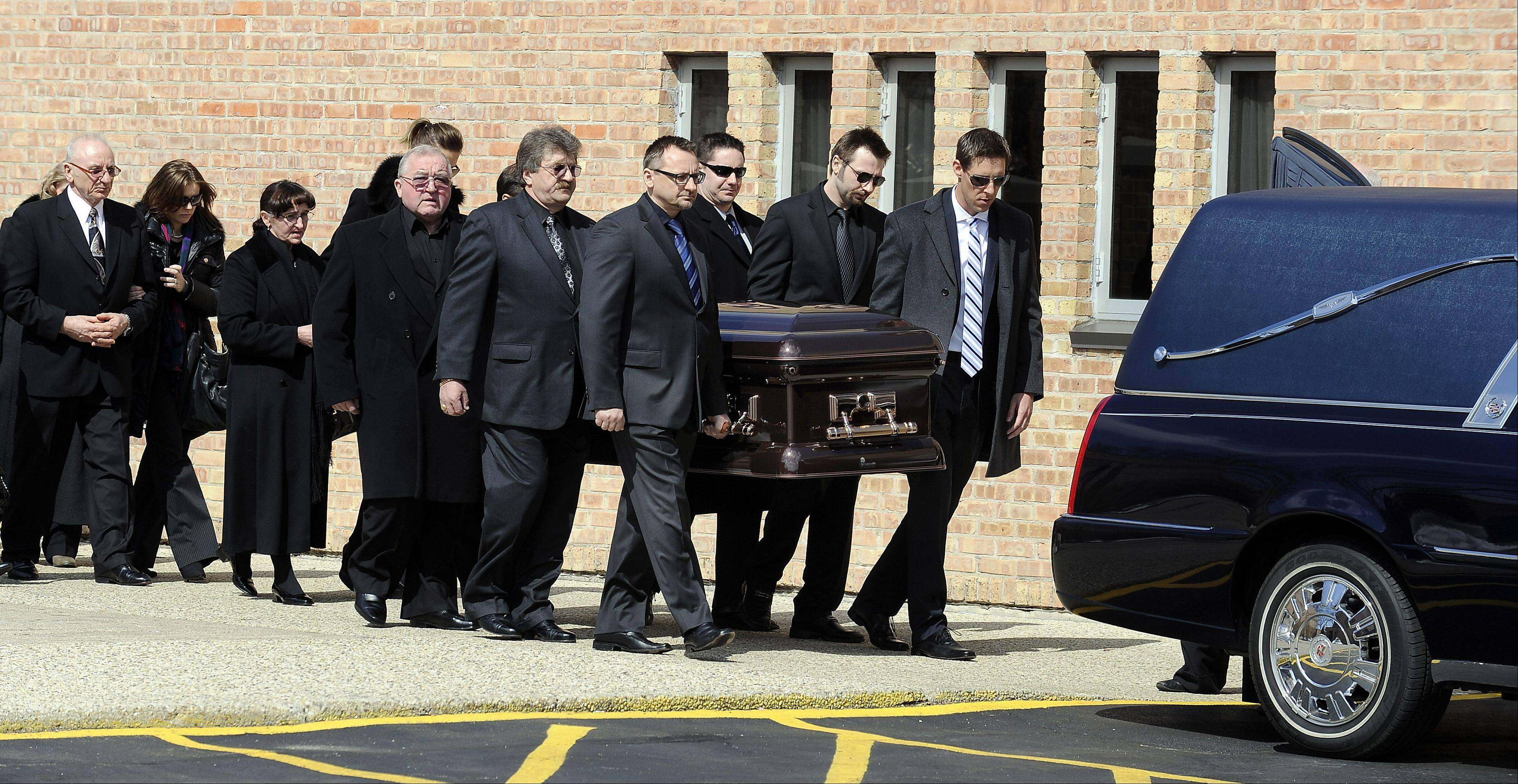 Pallbearers carry out the casket of Robert Komosa as his mother, Barbara, follows after his funeral service Saturday at St. Thomas Becket Church in Mt. Prospect.