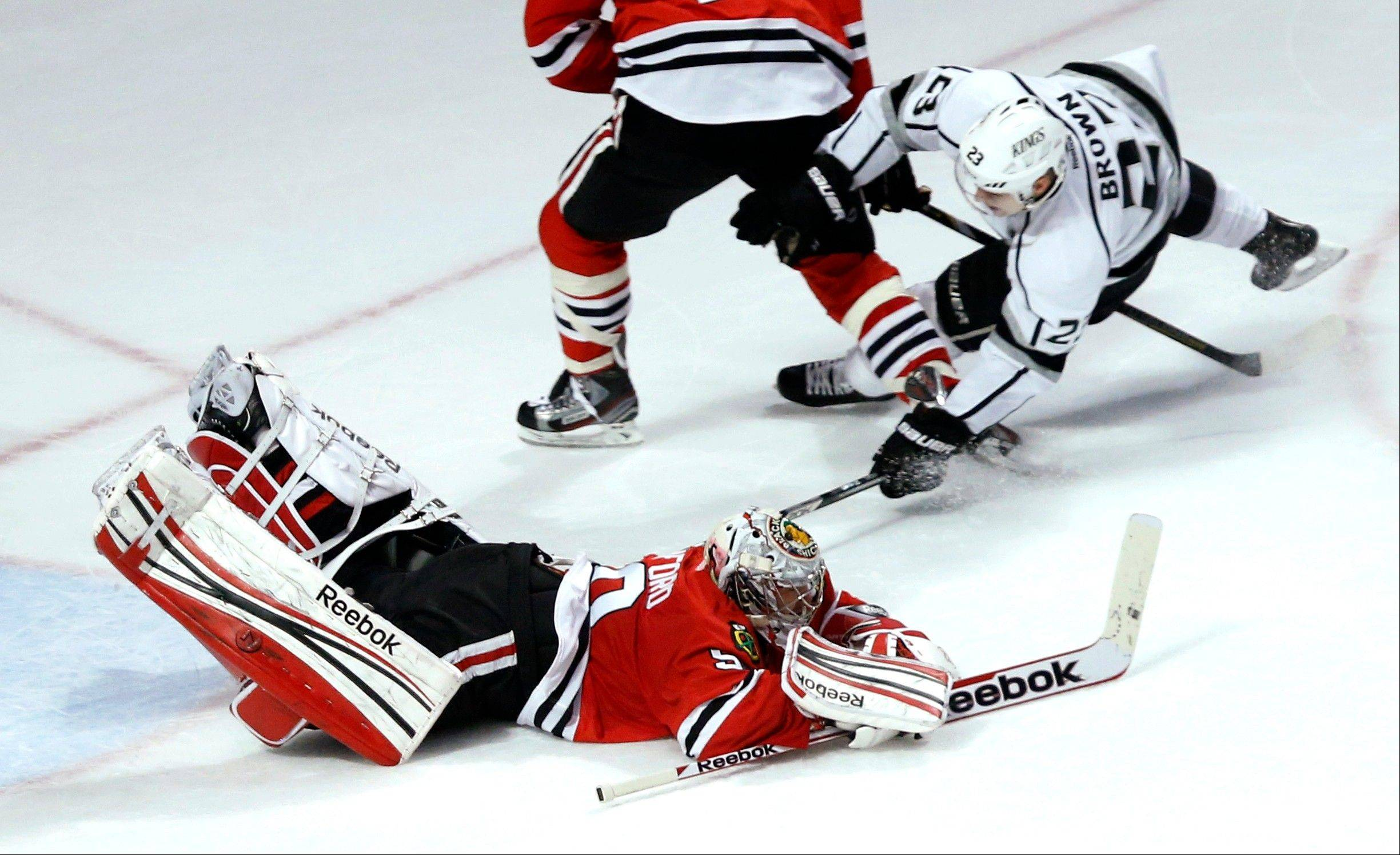 Chicago Blackhawks goalie Corey Crawford (50) dives on the puck, keeping Los Angeles Kings right wing Dustin Brown from getting a rebound shot off his shot on goal, during the second period.