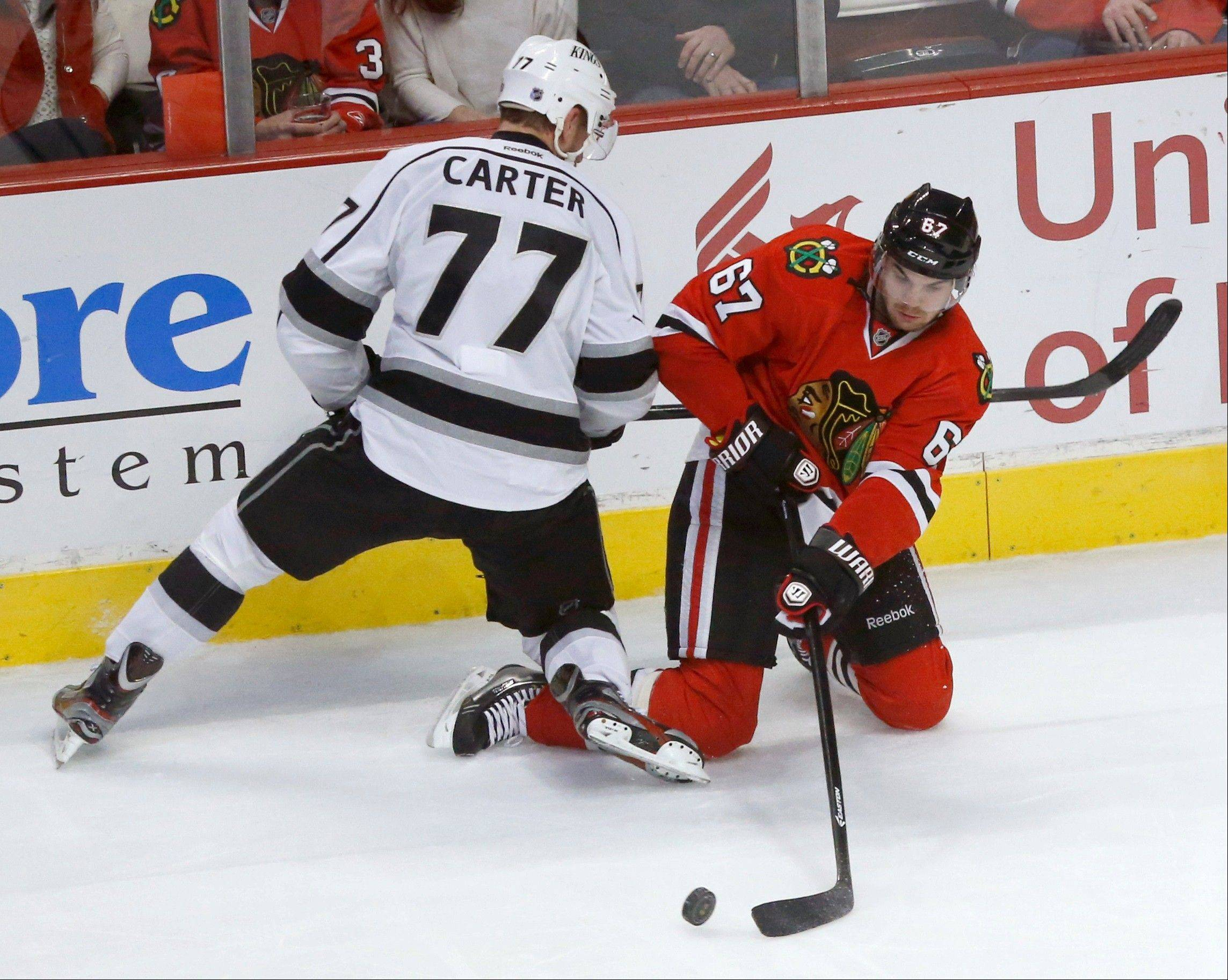 Chicago Blackhawks center Michael Frolik (67), of the Czech Republic, controls the puck from Los Angeles Kings center Jeff Carter (77) during the second period.