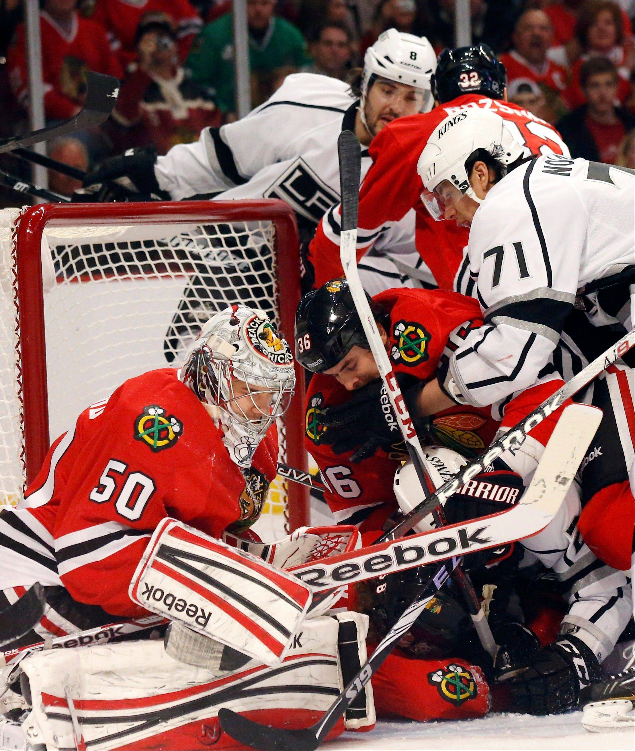 Several Chicago Blackhawks and Los Angeles Kings players crash into the goal crease near goalie Corey Crawford during the first period.