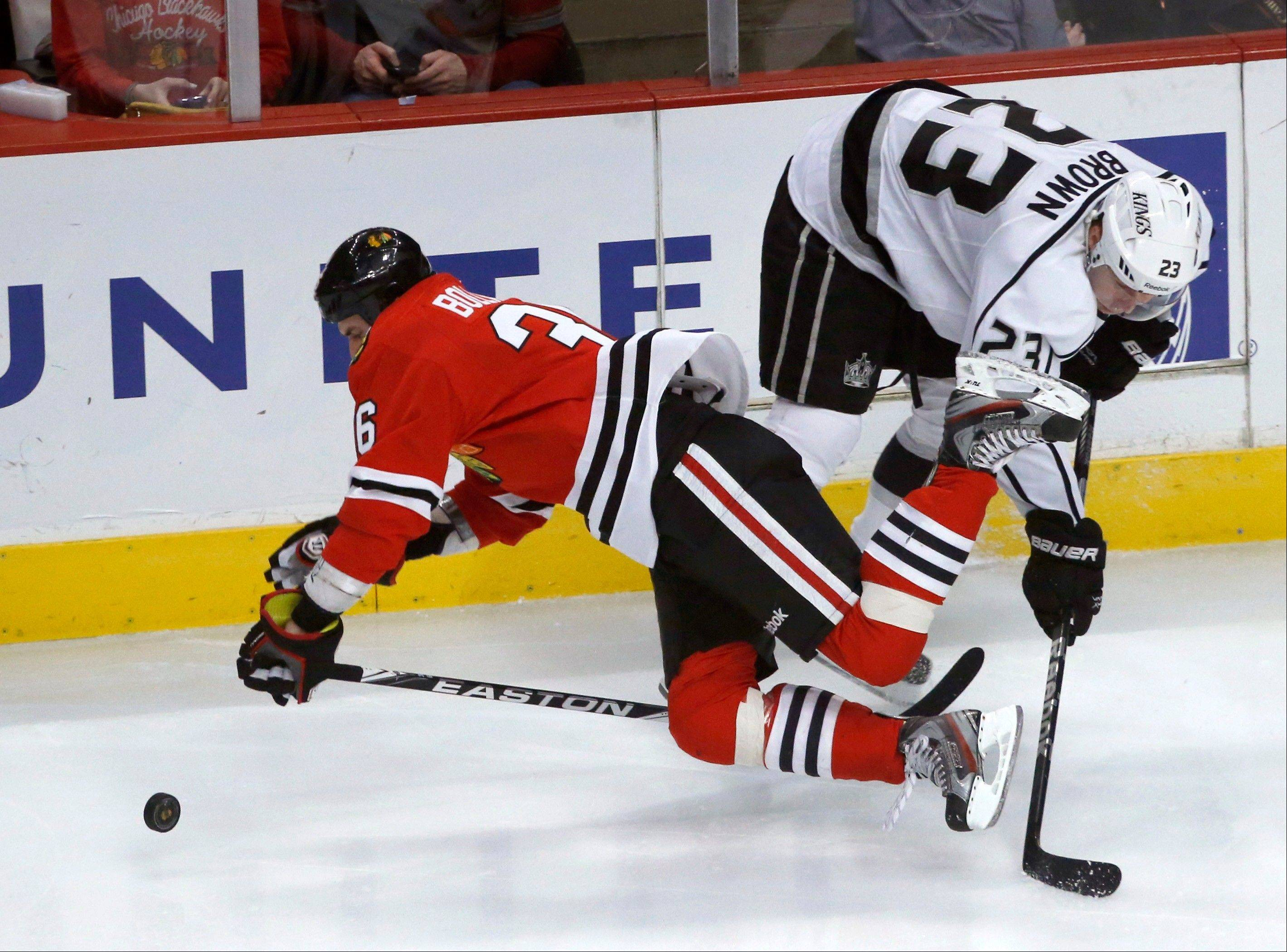 Chicago Blackhawks center Dave Bolland, left, falls over the stick of Los Angeles Kings right wing Dustin Brown during the third period of an NHL hockey game, Monday, March 25, 2013, in Chicago. The Kings won 5-4.