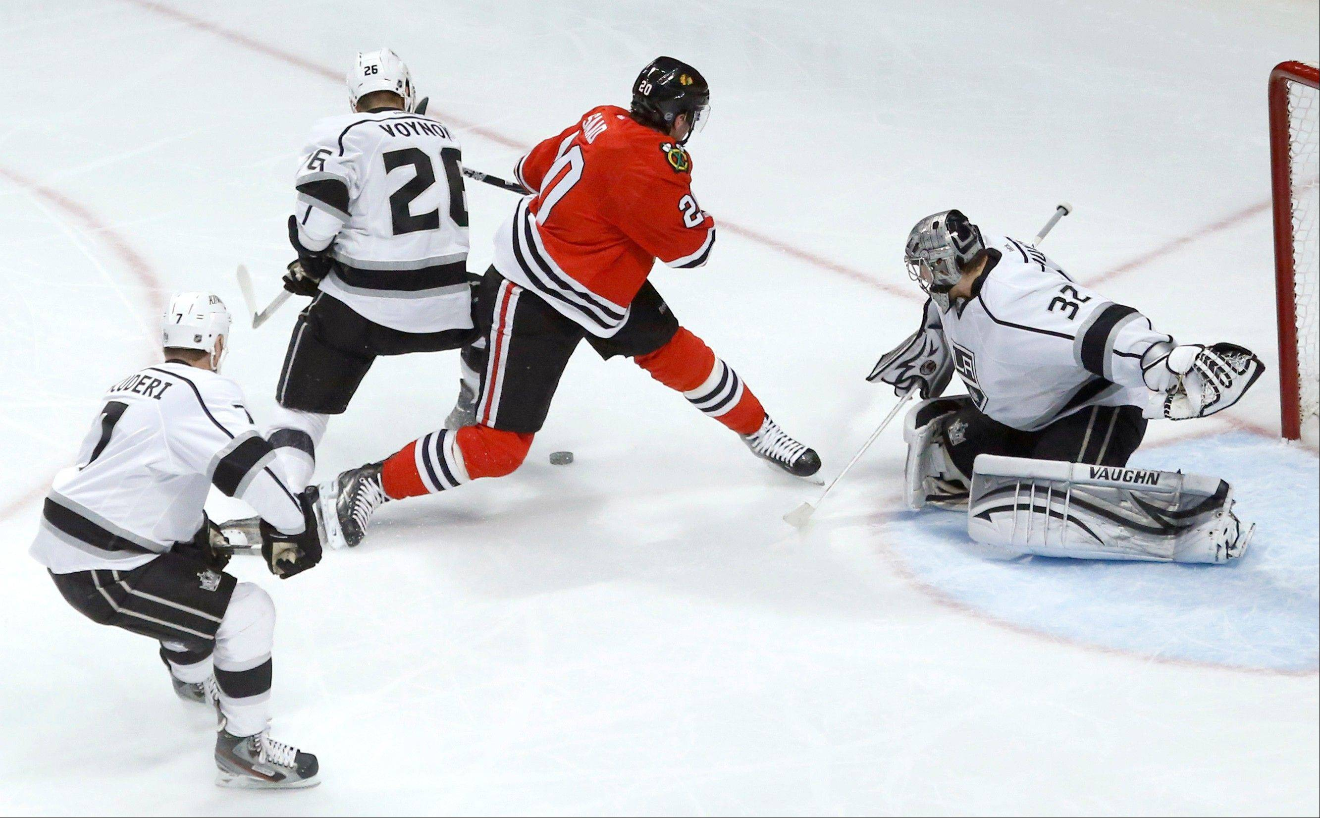 Los Angeles Kings defenseman Slava Voynov (26), of Russia, keeps Chicago Blackhawks left wing Brandon Saad from getting a shot on goal as Rob Scuderi (7) and goalie Jonathan Quick watch during the second period.