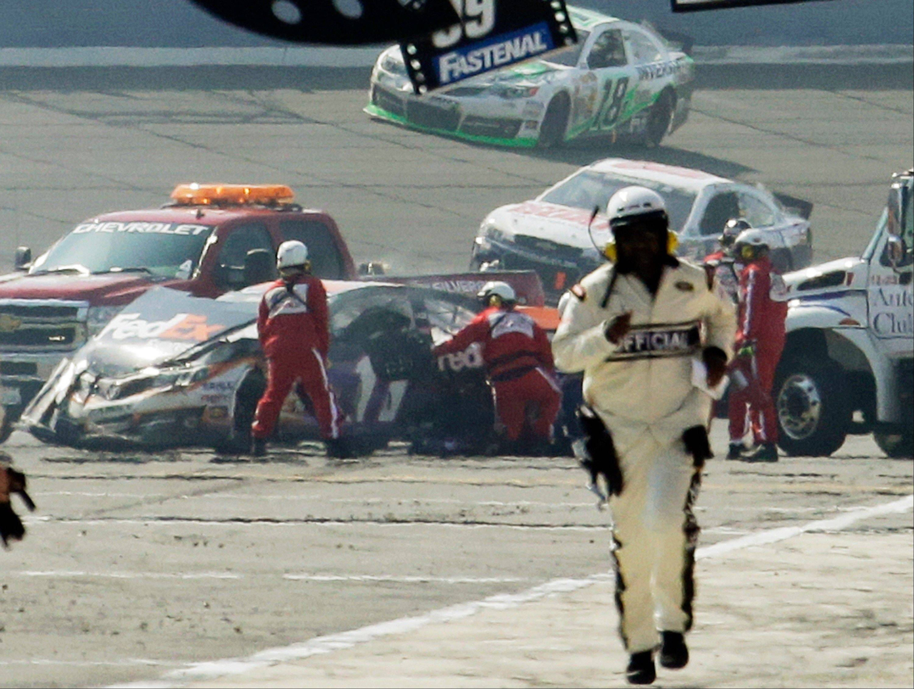 Rescue workers tend to the wreckage of the No. 11 FedEx Express Toyota driven by Denny Hamlin after he collided with Joey Logano Sunday on the final lap of the NASCAR Sprint Cup series auto race in Fontana, Calif. The pair had been battling for the lead the last three laps. The No. 18 car of Kyle Busch passes behind on its victory lap.