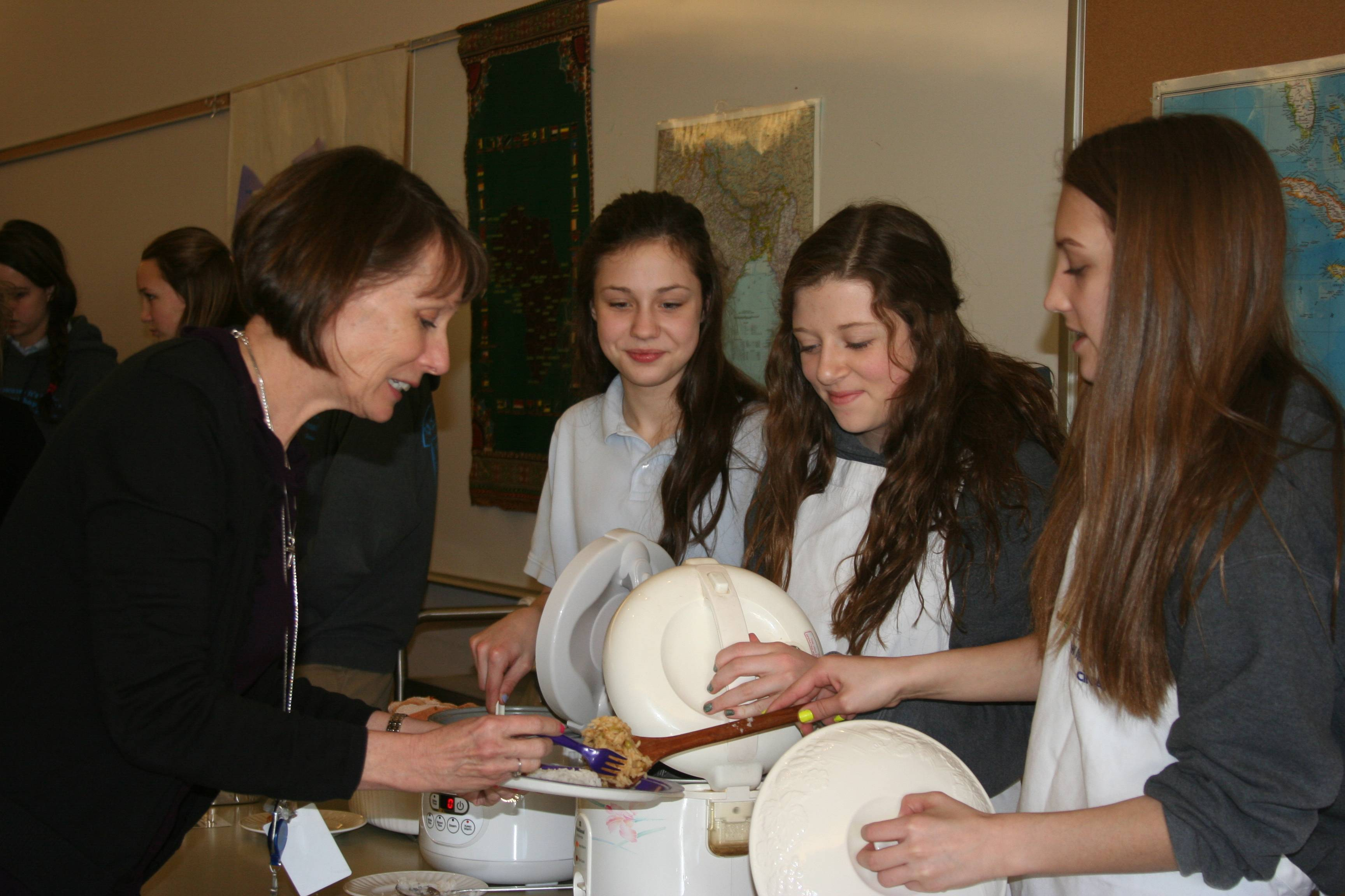 Holy Family Academy 8th grade students raise awareness of world poverty by cooking meals typically found in developing countries. Pictured from left, Bethany, Shannon and Mia serving Mrs. Roberta Muran.