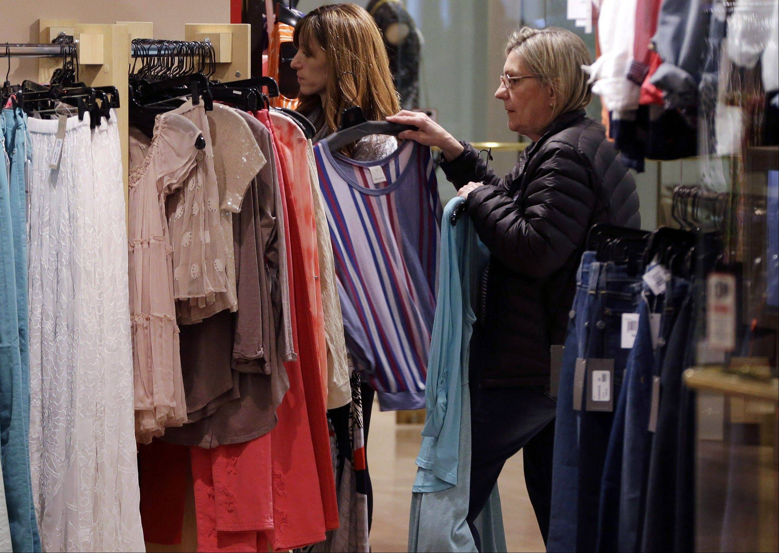Shoppers look at clothing on sale at the Footloose store in Mt. Lebanon, Pa. The Conference Board, a New York-based private research group, said its reading of consumer confidence fell in March after rebounding last month.