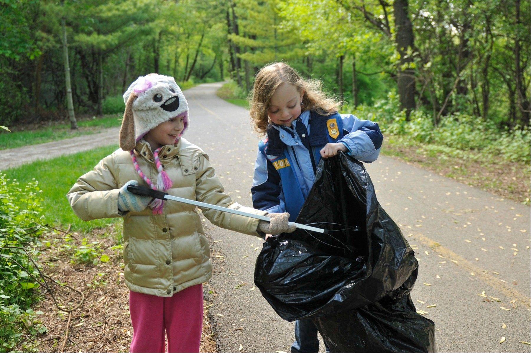 A pair of young volunteers helps clean up along the Gilman Trail during a previous year�s event. The annual Spring Spruce-Up will be held on April 20 at six different Fox Valley Park District sites.