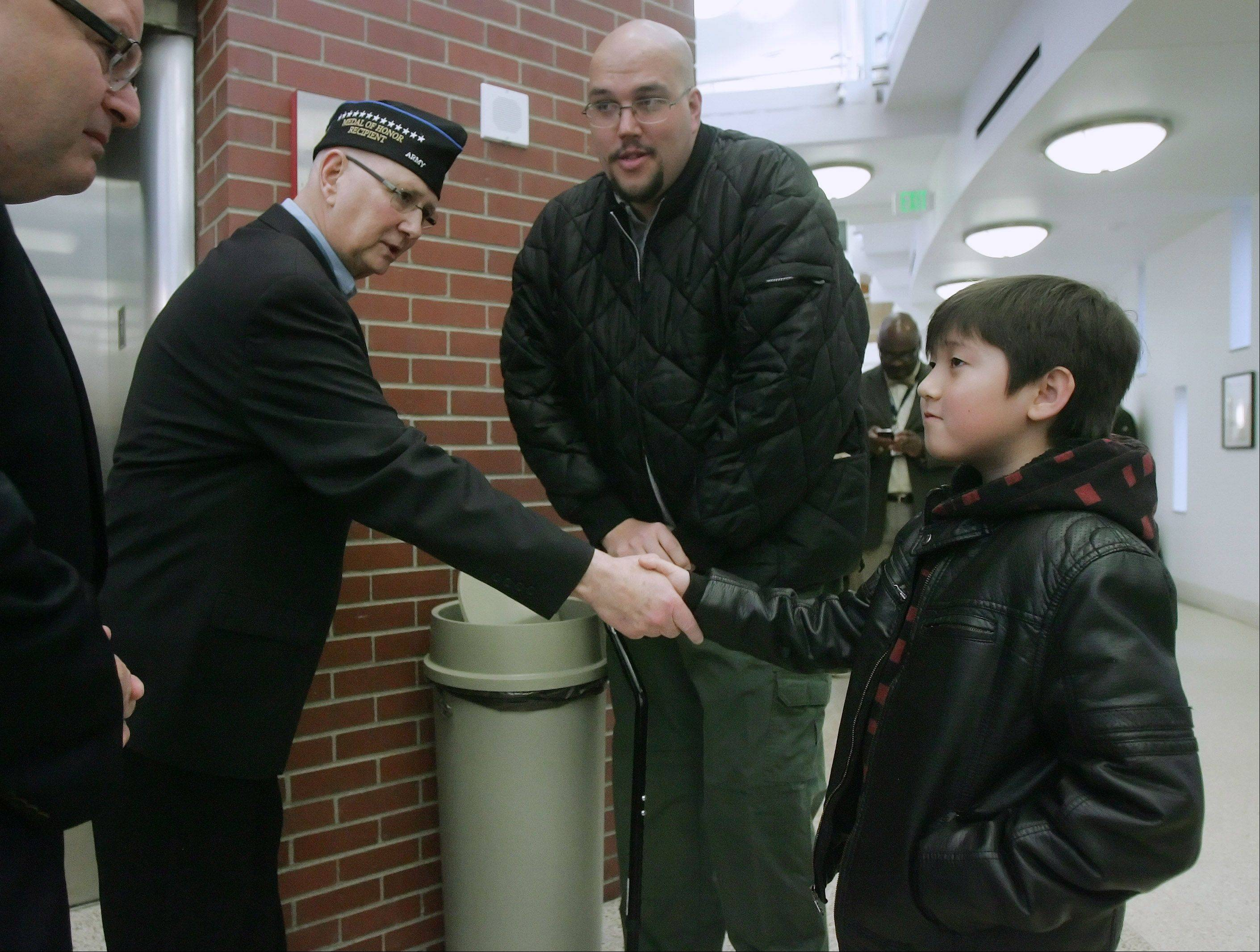 Medal of Honor recipient Allen Lynch, of Gurnee, shakes hands with 10-year-old Jinu Puclik, of Glenview, and his dad, Tim, at the Capt. James A. Lovell Federal Health Care Center Monday. Lynch was recognized during a ceremony commemorating National Medal of Honor Day.