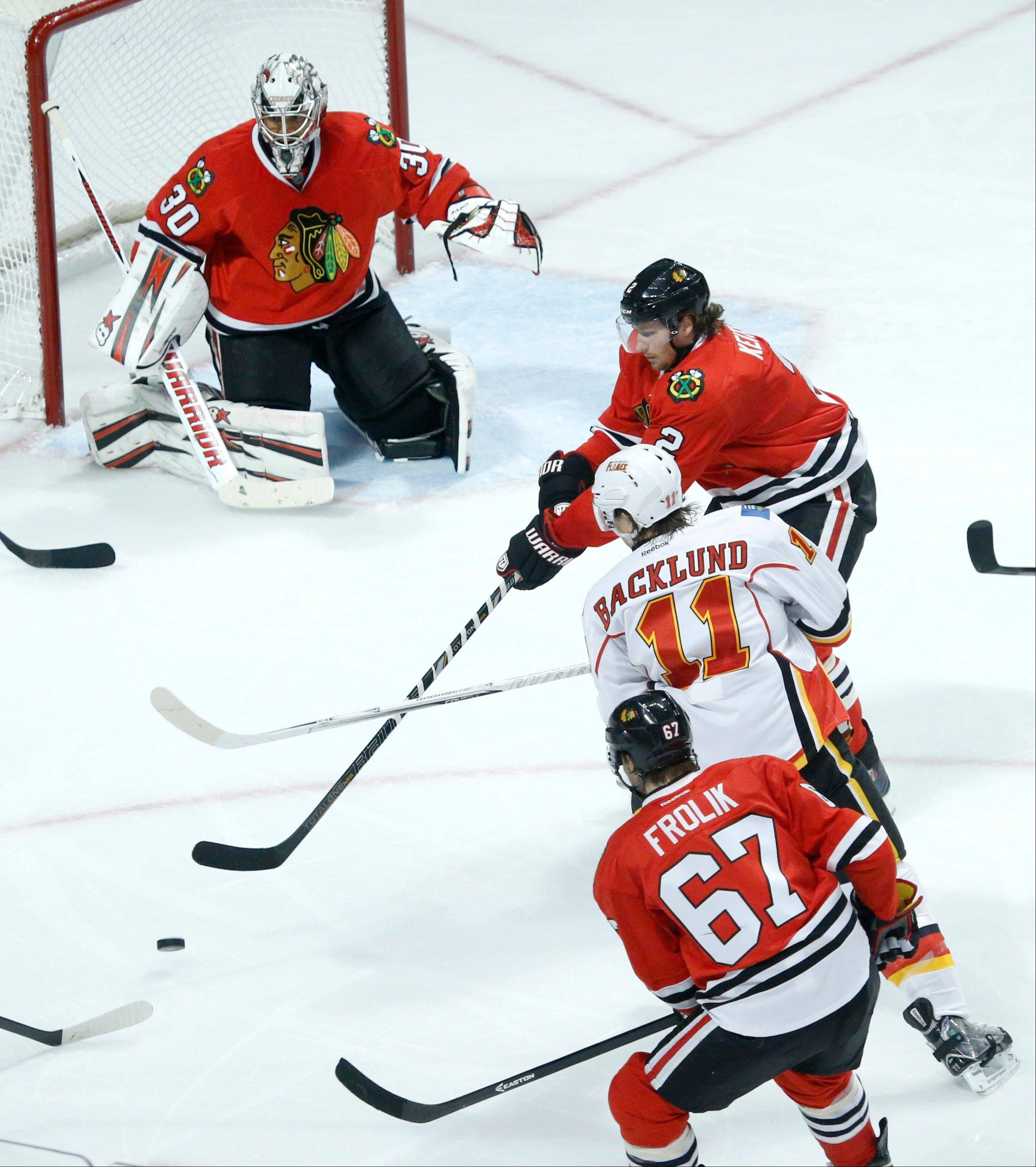 Blackhawks defenseman Duncan Keith (2) keeps Calgary Flames center Mikael Backlund, from Sweden, from getting a shot on goal as center Michael Frolik (67), from the Czech Republic, and goalie Ray Emery watch during the Blackhawks victory over the Flames Tuesday night at the United Center.