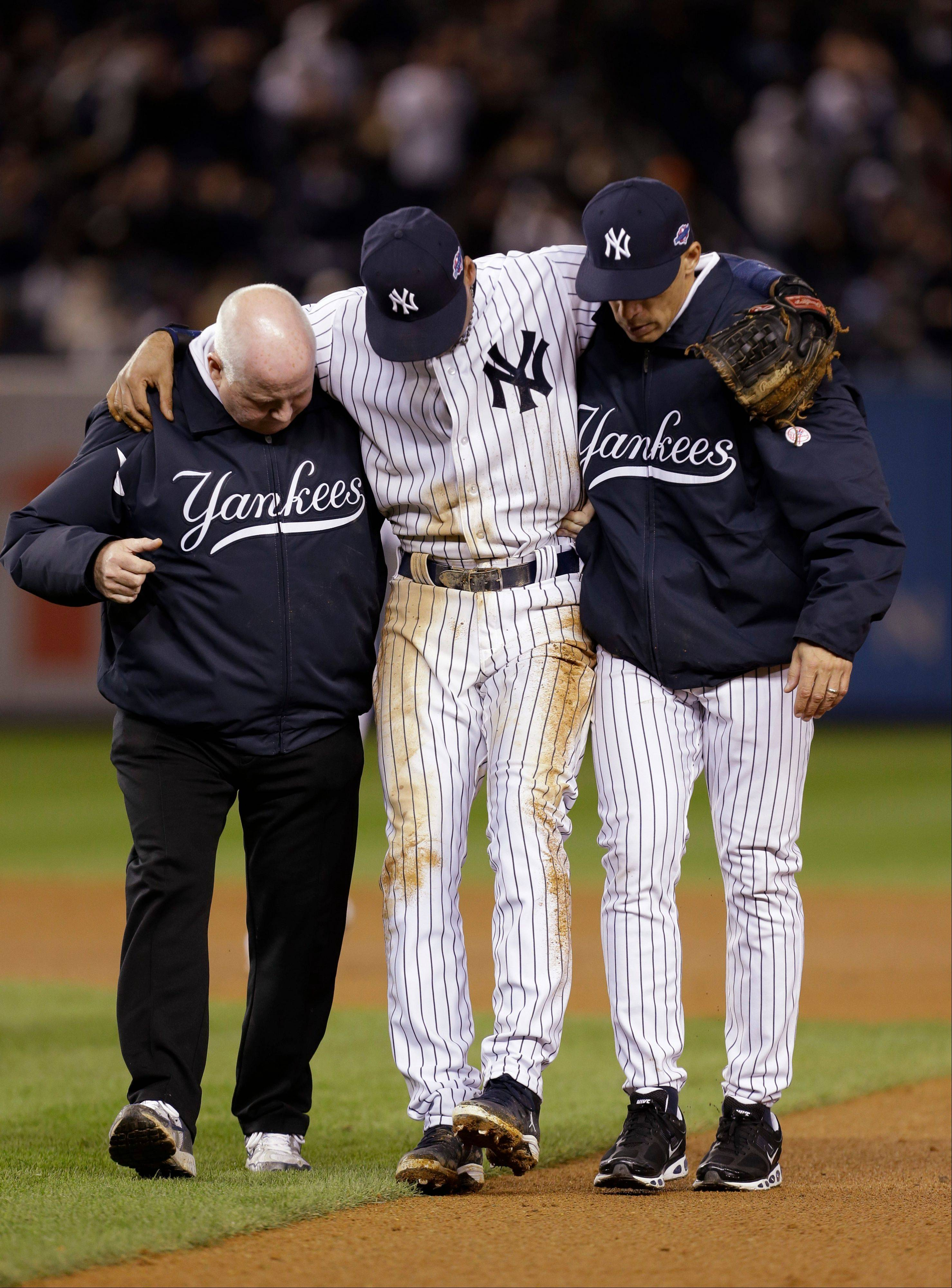 FILE - In an Oct. 14, 2012 file photo trainer Steve Donohue, left, and New York Yankees manager Joe Girardi, right, help Yankees' Derek Jeter off the field after he injured himself during Game 1 of the American League championship series in New York. Derek Jeter will likely join Alex Rodriguez, Mark Teixeira and Curtis Granderson on the New York Yankees' star-studded disabled list for the season opener against the Boston Red Sox on April 1, 2013. (AP Photo/Paul Sancya )