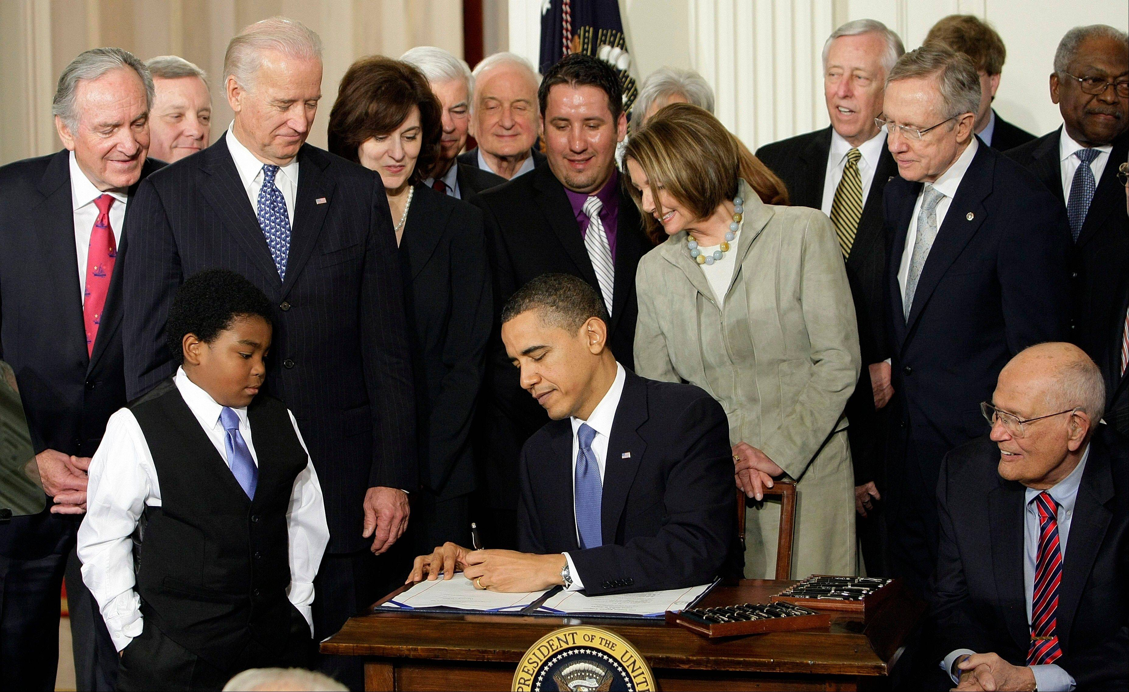In this March 23, 2010, file photo, President Barack Obama signs the health care bill at the White House. Medical claims costs, the biggest driver of health insurance premiums, will jump an average 32 percent for individual policies under the overhaul, according to a study by the nation's leading group of financial risk analysts.