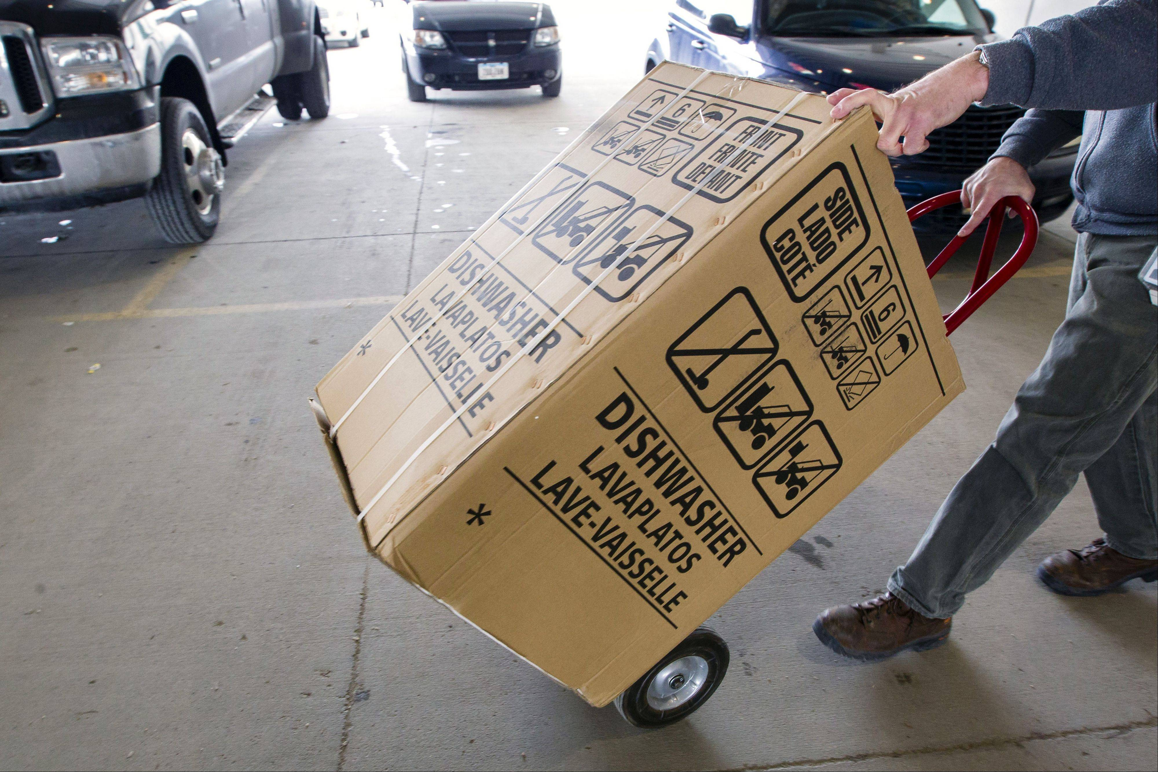 An employees carts a dishwasher to a customer's vehicle at the loading docks of Nebraska Furniture Mart in Omaha, A surge in commercial aircraft demand pushed orders for U.S. long-lasting manufactured goods up sharply in February.