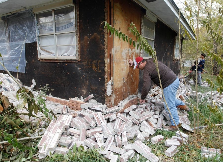 Chad Devereaux examines bricks that fell from three sides of his in-laws home in Sparks, Okla. on Nov. 6, 2011 after two earthquakes hit the area in less than 24 hours. A team of scientists have determined that a 5.6 magnitude quake in Oklahoma in 2011 was caused when oil drilling waste was injected deep underground.