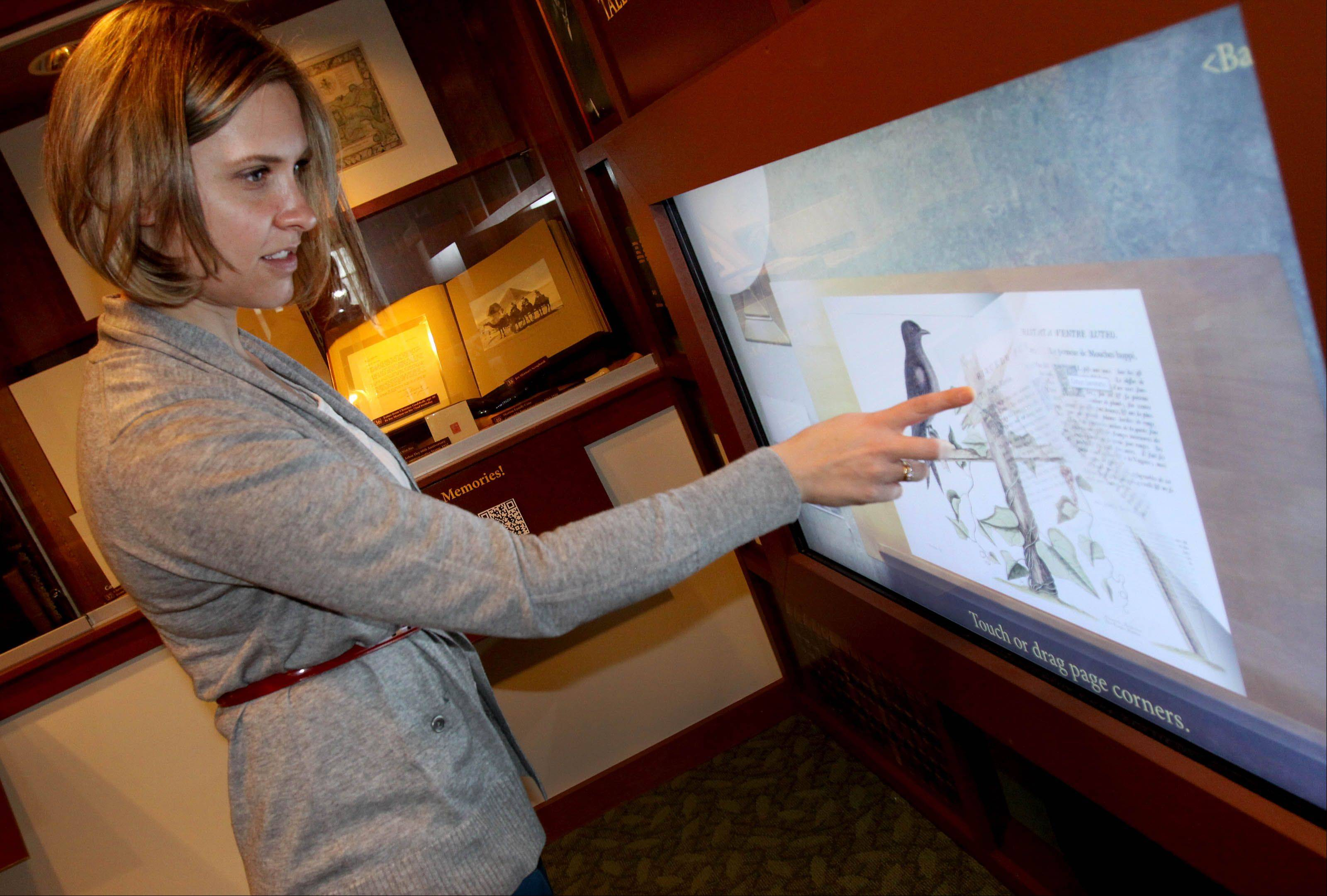 Sarah Clark, public relations specialist for Morton Arboretum, demonstrates how books that are too fragile to be handled can be paged through on a touch screen.