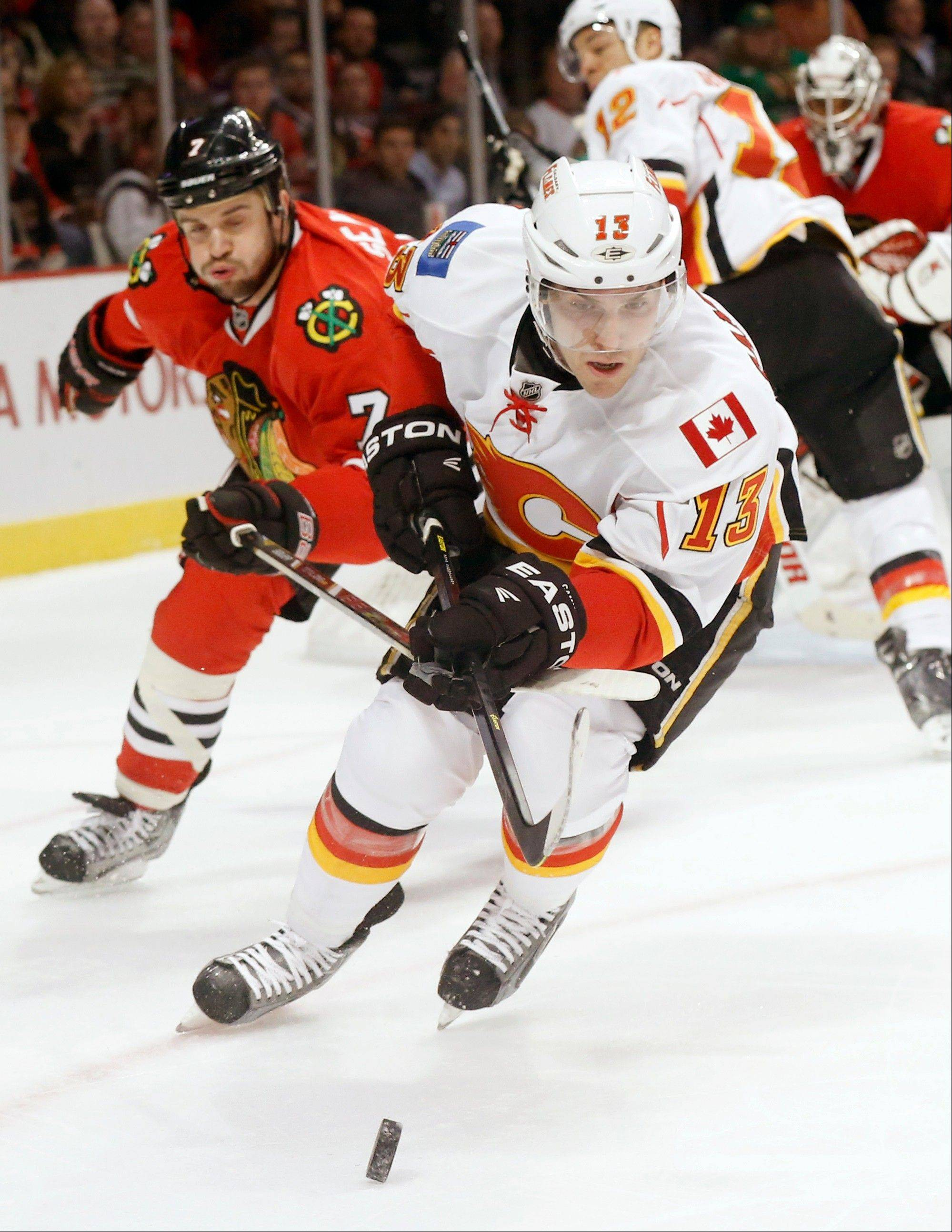Calgary Flames left wing Mike Cammalleri (13) and Chicago Blackhawks defenseman Brent Seabrook (7) chase after a loose puck during the first period of an NHL hockey game Tuesday, March 26, 2013 in Chicago.