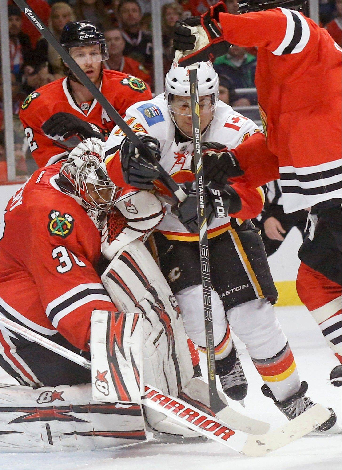 Calgary Flames right wing Jarome Iginla, center, is sandwiched between Chicago Blackhawks goalie Ray Emery (30) and Brent Seabrook during the first period of an NHL hockey game Tuesday, March 26, 2013 in Chicago.