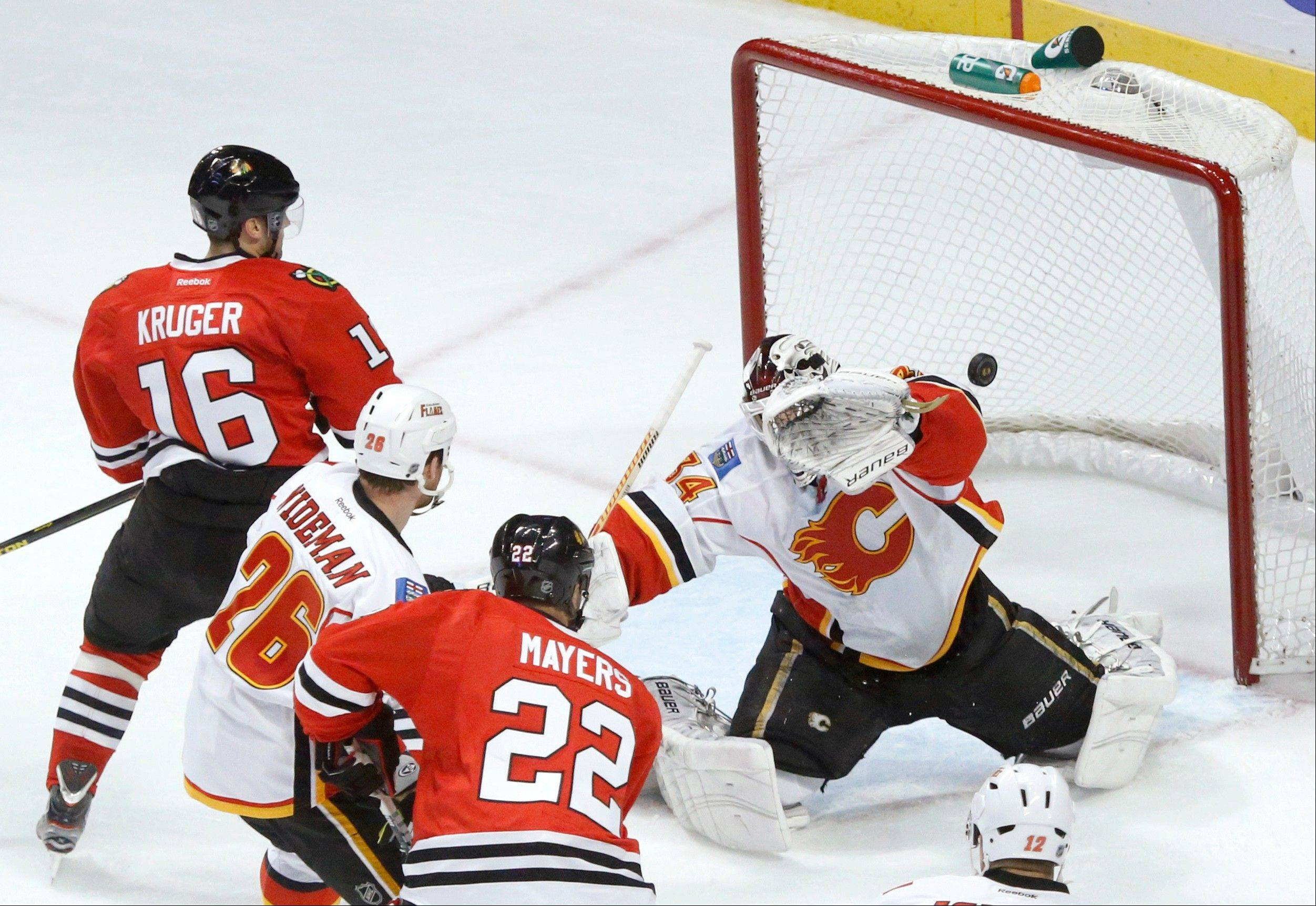Calgary Flames goalie Miikka Kiprusoff, from Finland, is unable to make a glove save on a goal by Chicago Blackhawks defenseman Brent Seabrook as Marcus Kruger (16), from Sweden, Dennis Wideman, and Jamal Mayers watch during the second period of an NHL hockey game Tuesday, March 26, 2013 in Chicago.