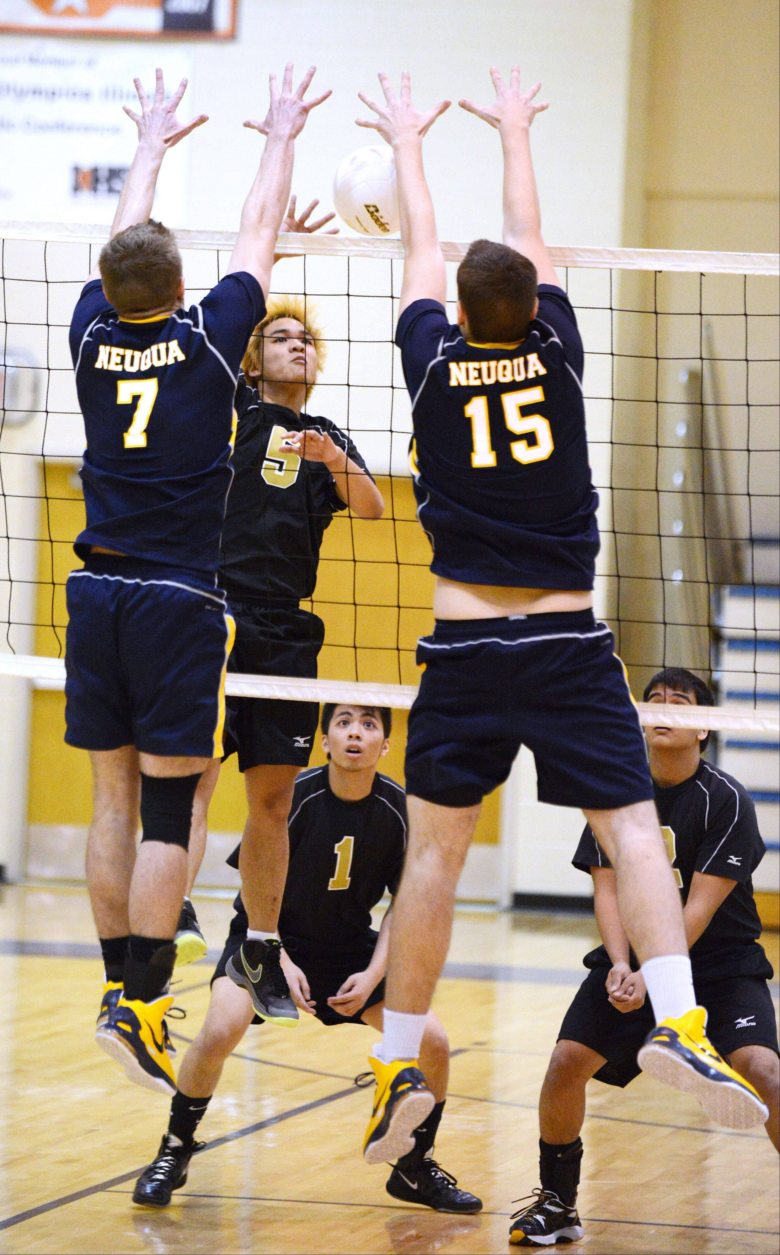 Lester Dela Cruz of Streamwood hits the ball at two Neuqua Vally defenders during the Streamwood at Neuqua Valley boys volleyball game Tuesday. The defenders were Callahan Rafferty,left, and Drew McKissick of Neuqua.