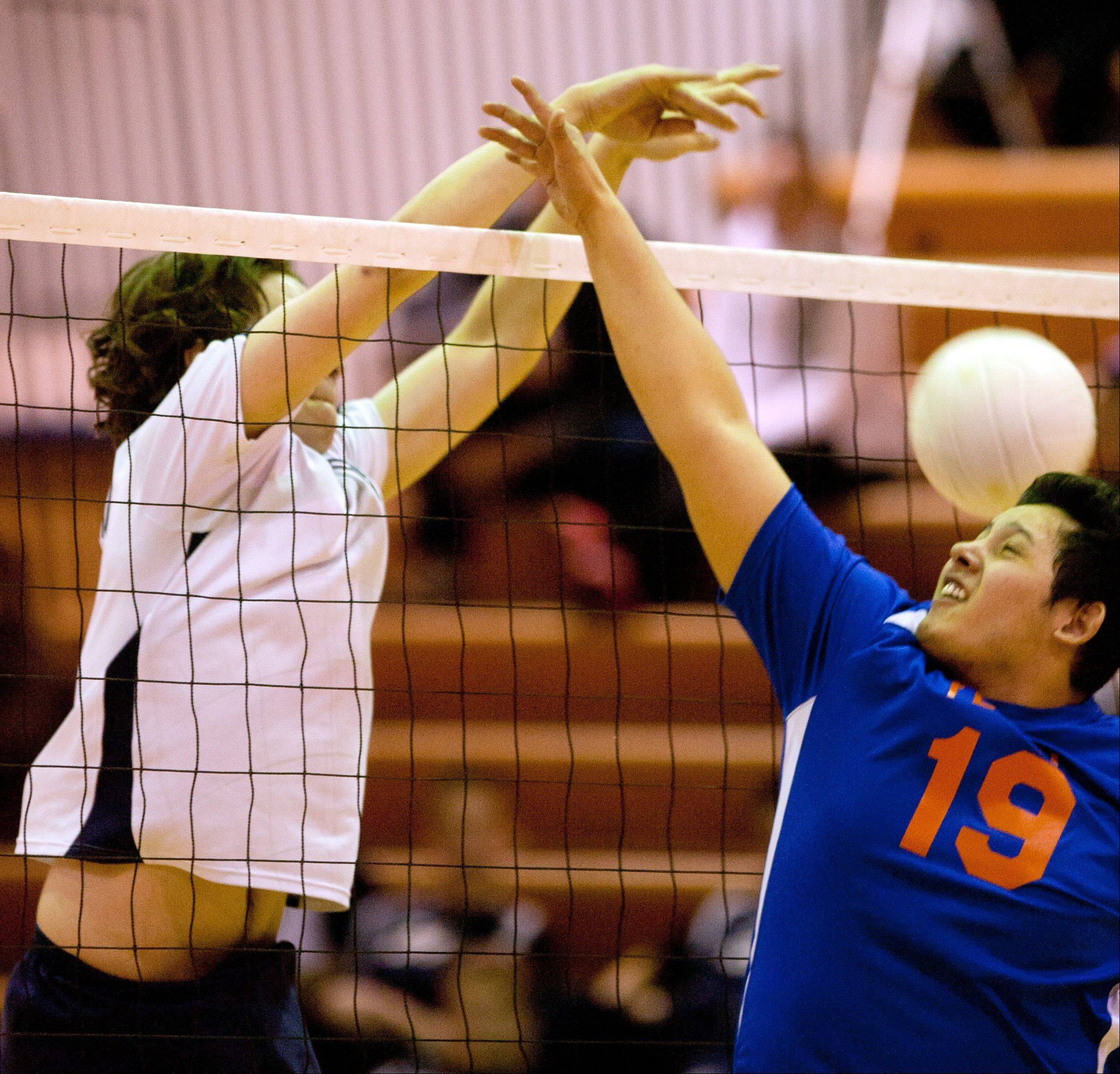 West Chicago's Gus MacPherson, left, battles Fenton's Carlos Campos, right, during boys volleyball action Tuesday.