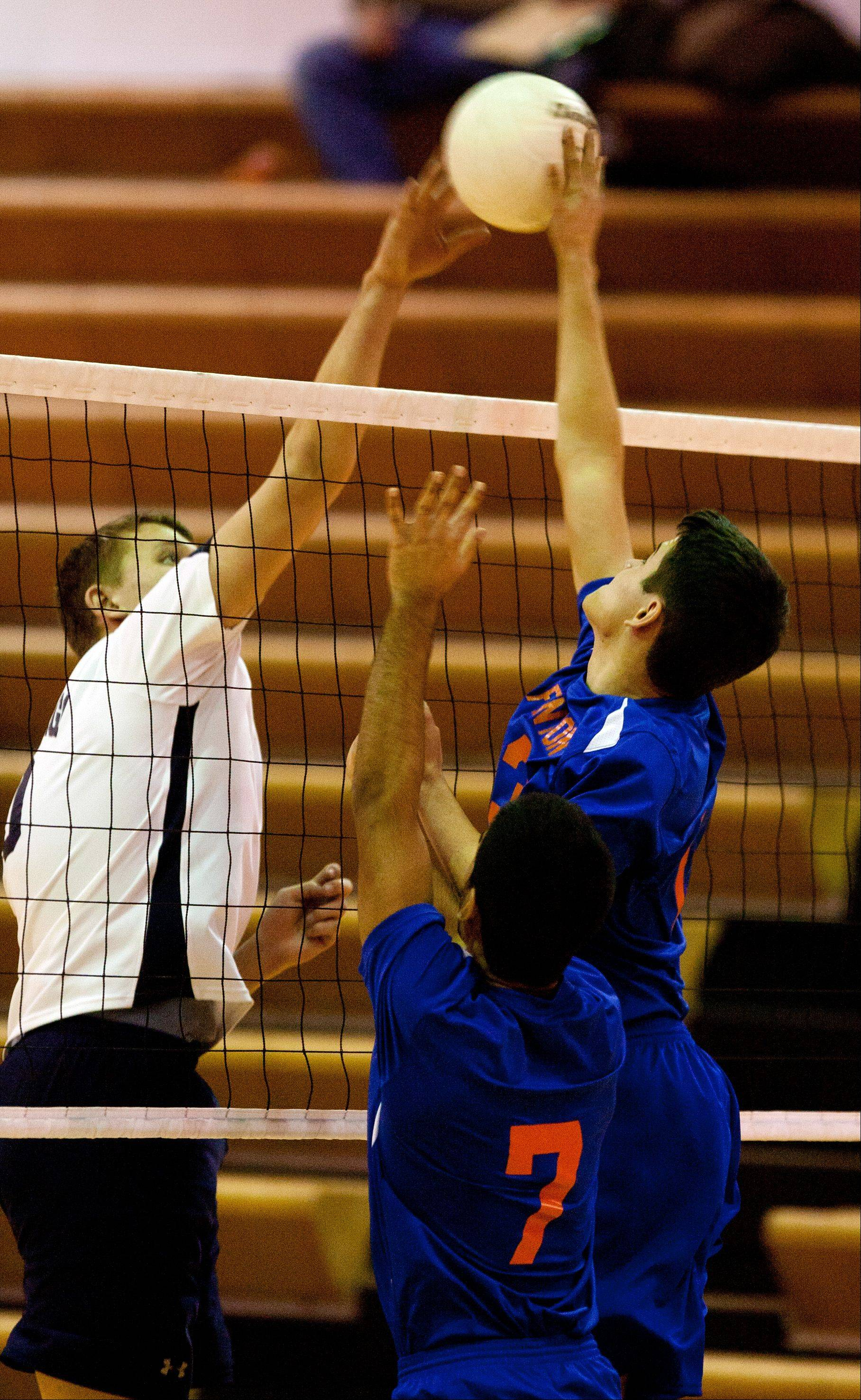West Chicago's Joe Pinkevich, left, battles Fenton's Nathan Rivera, right, at the net during boys volleyball action Tuesday.