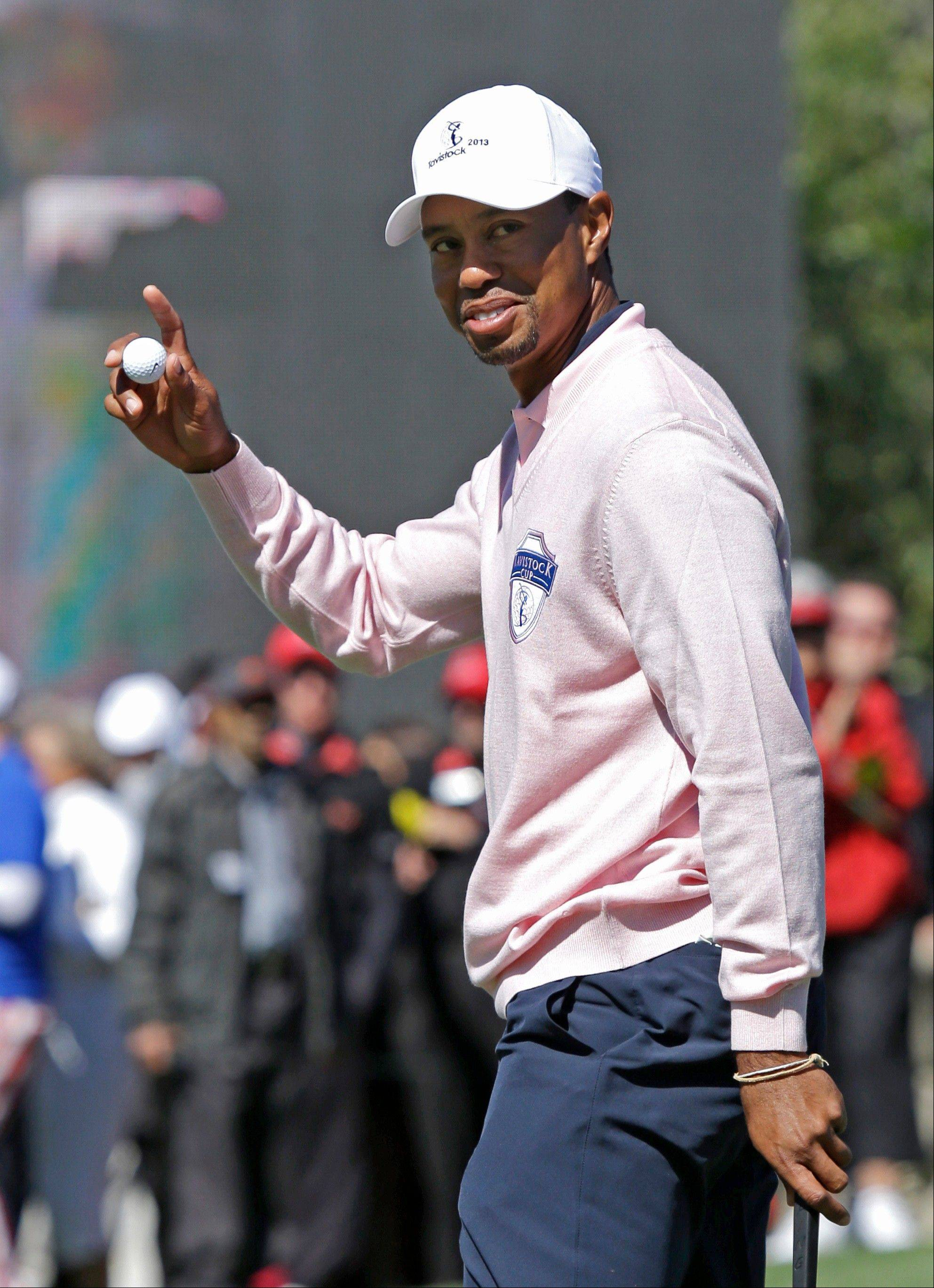 Tiger Woods waves to the gallery after his putt on the 18th green during the Tavistock Cup golf tournament, Tuesday, March 26, 2013, in Windermere, Fla.