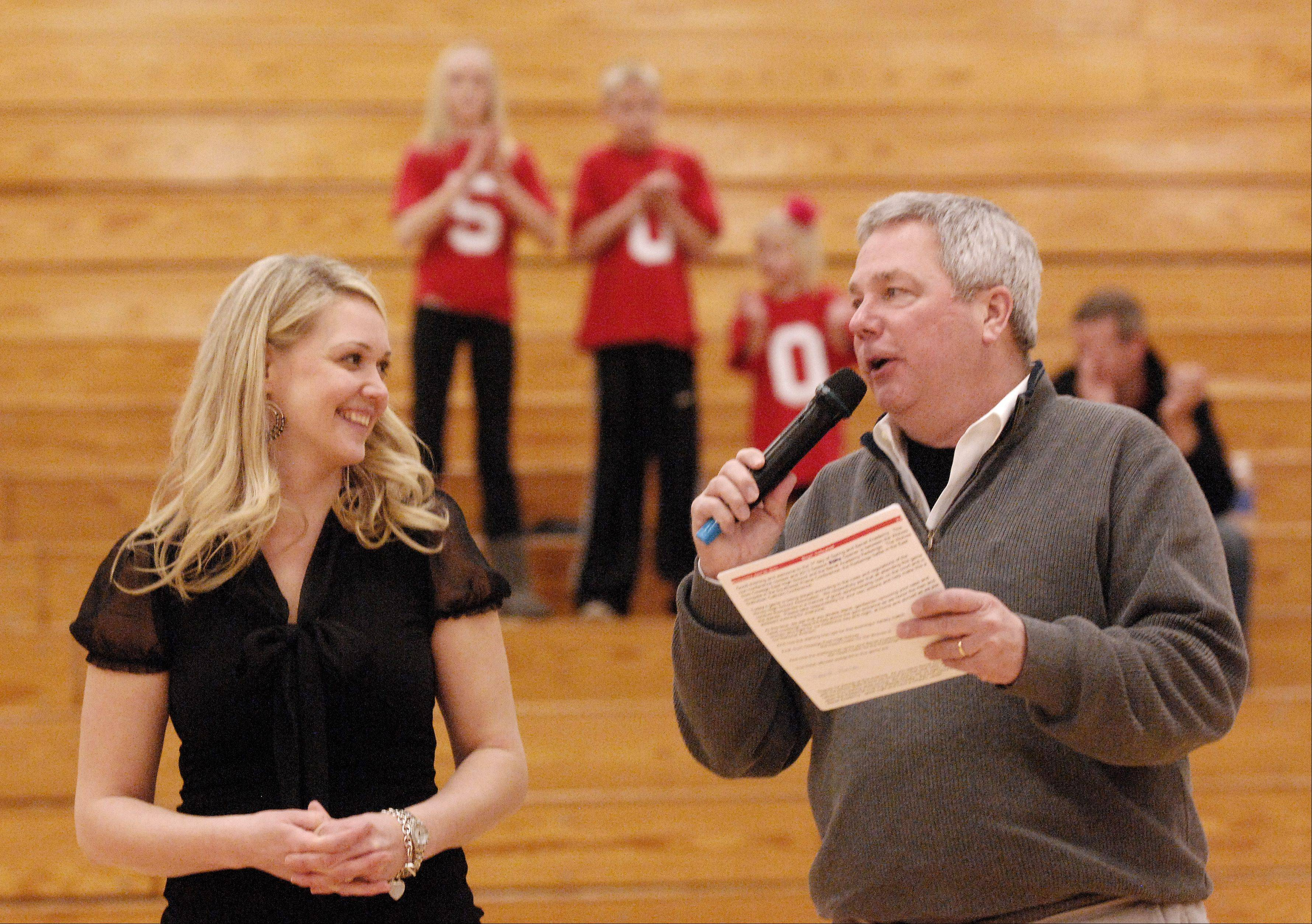 Announcer Bill Dorn honors Benet Academy head boys volleyball coach Amy Van Eekeren for her 500th win Wednesday. Her children spell out 500 with their shirts in the bleachers.
