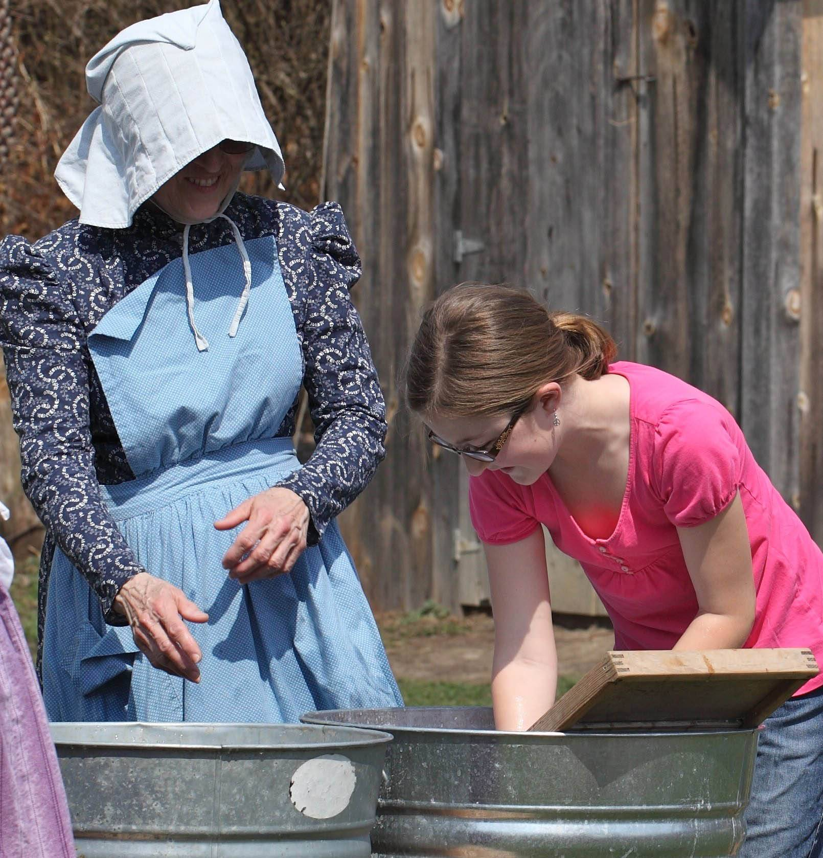 A volunteer demonstrates 1880s life to a visitor at last year's Springtime on the Farm.