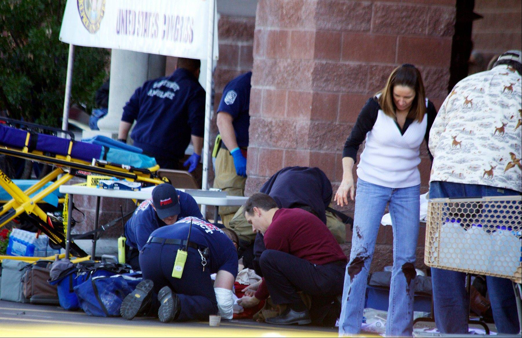 Emergency personnel attend to a shooting victim outside a shopping center in Tucson, Ariz. in this Saturday, Jan. 8, 2011 photo taken where U.S. Rep. Gabrielle Giffords, D-Ariz., and others were shot as the congresswoman was meeting with constituents.
