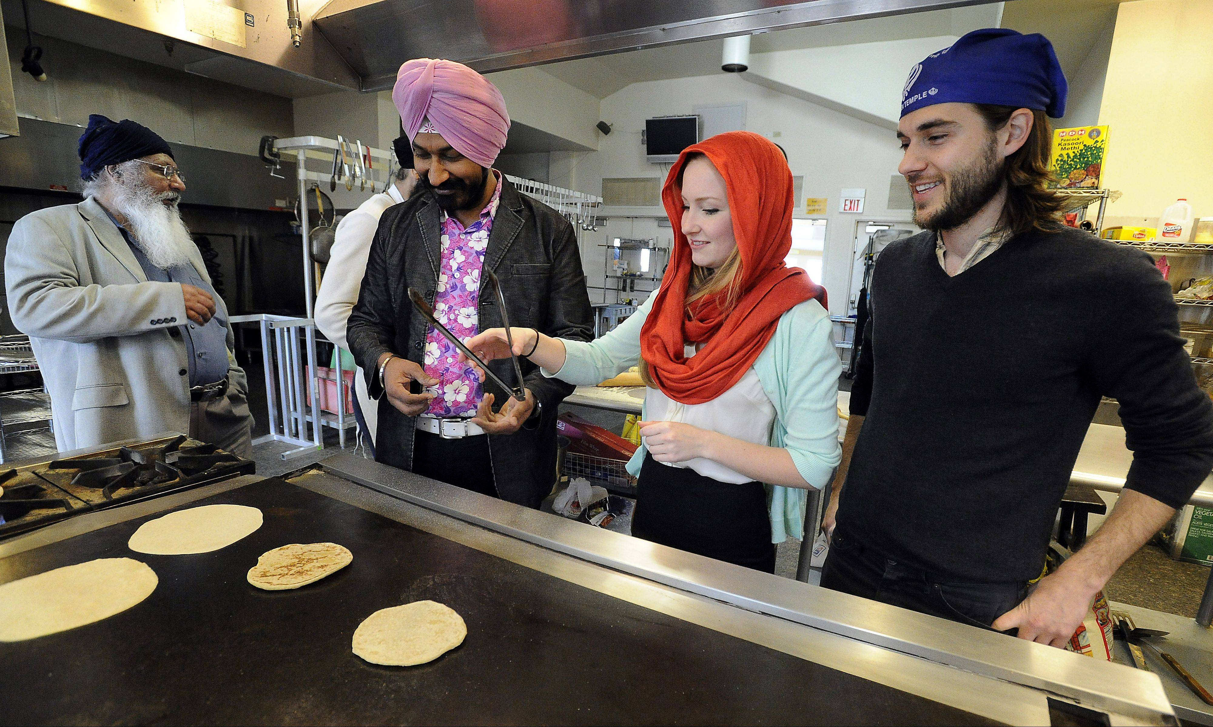 Gurucharan Singh, who starred in a popular Indian sitcom, makes chapatis with former co-star Kari Irwin and Scott Footer, both of Palatine, while Iqbal Sodhi looks on at the Sikh Religious Society Temple in Palatine.