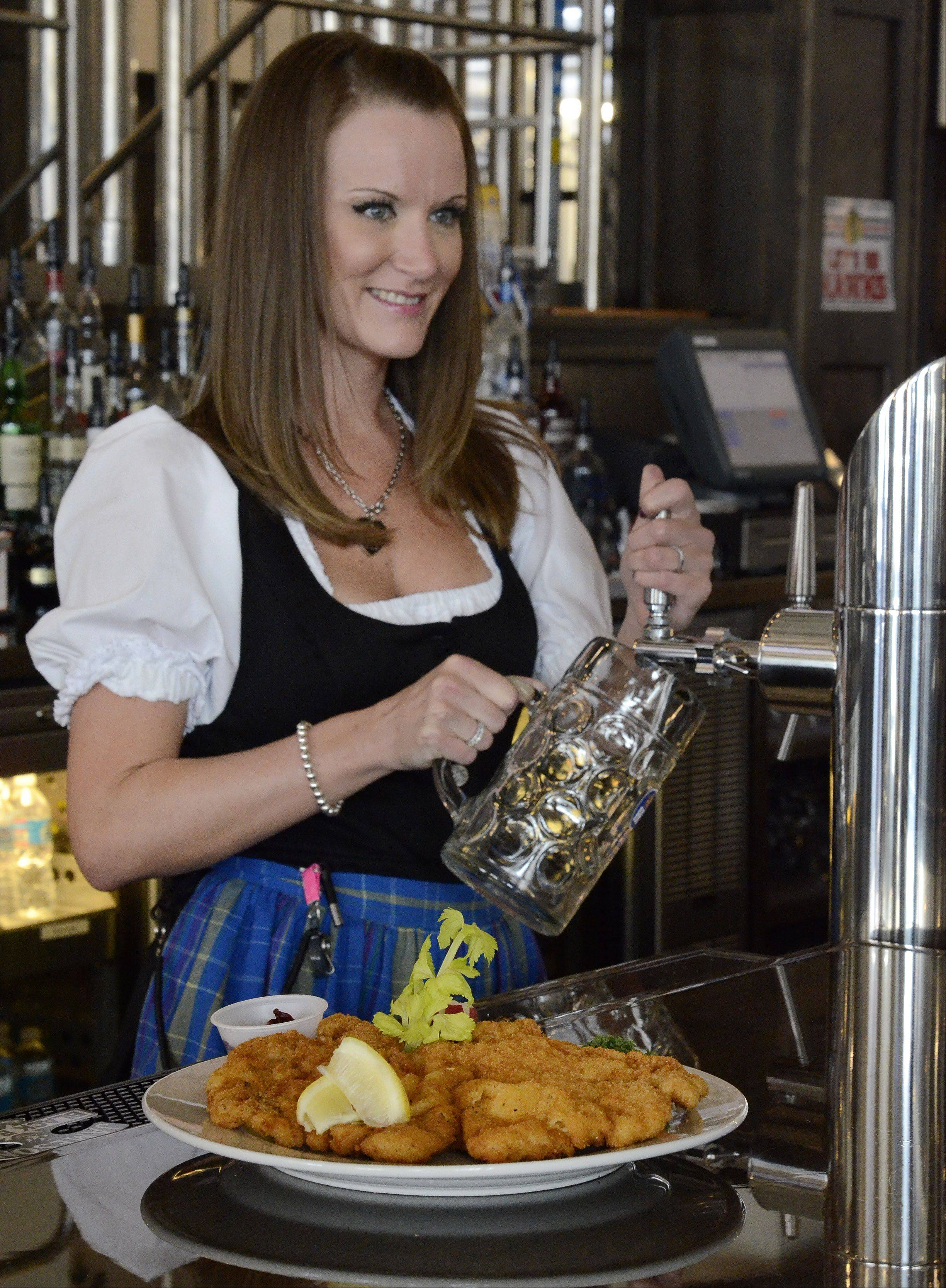 Kelly Gundlach pours a beer in front of a plate of Schnitzel Weiner Art, a crispy breaded pork cutlet, at Hofbrauhaus in Rosemont.