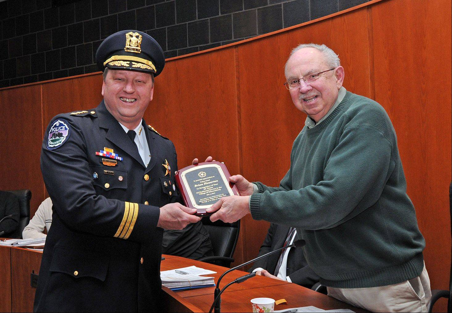 Outgoing Schaumburg Police Chief Brian Howerton, left, was recognized by Mayor Al Larson and other village officials Tuesday for his 32 years of service to the village.