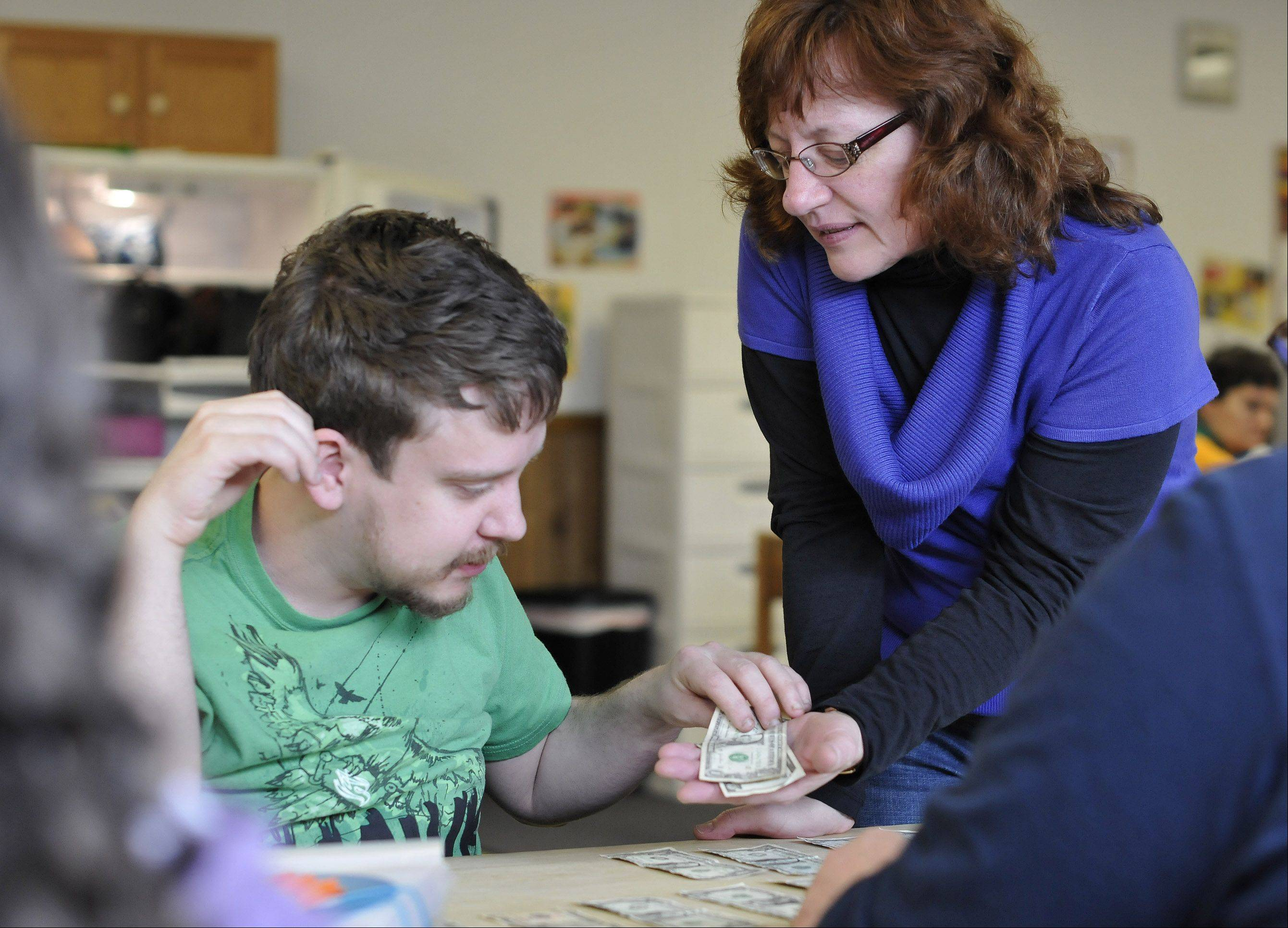 Marilyn Flanagan, president and executive director of RRAF, a Lombard nonprofit that provides day programming for adults with disabilities, helps client Michael Hodges count cash during a group activity.