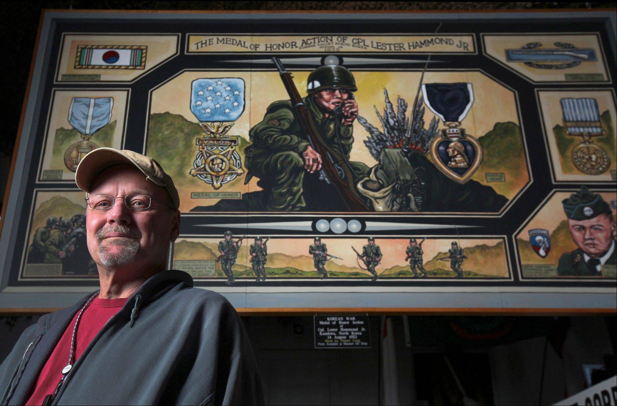 Bob Craig, curator of the All Wars Museum at the Illinois Veterans Home in Quincy stands in front of a mural he painted depicting the heroics of Medal of Honor recipient Lester Hammond Jr. of Quincy.