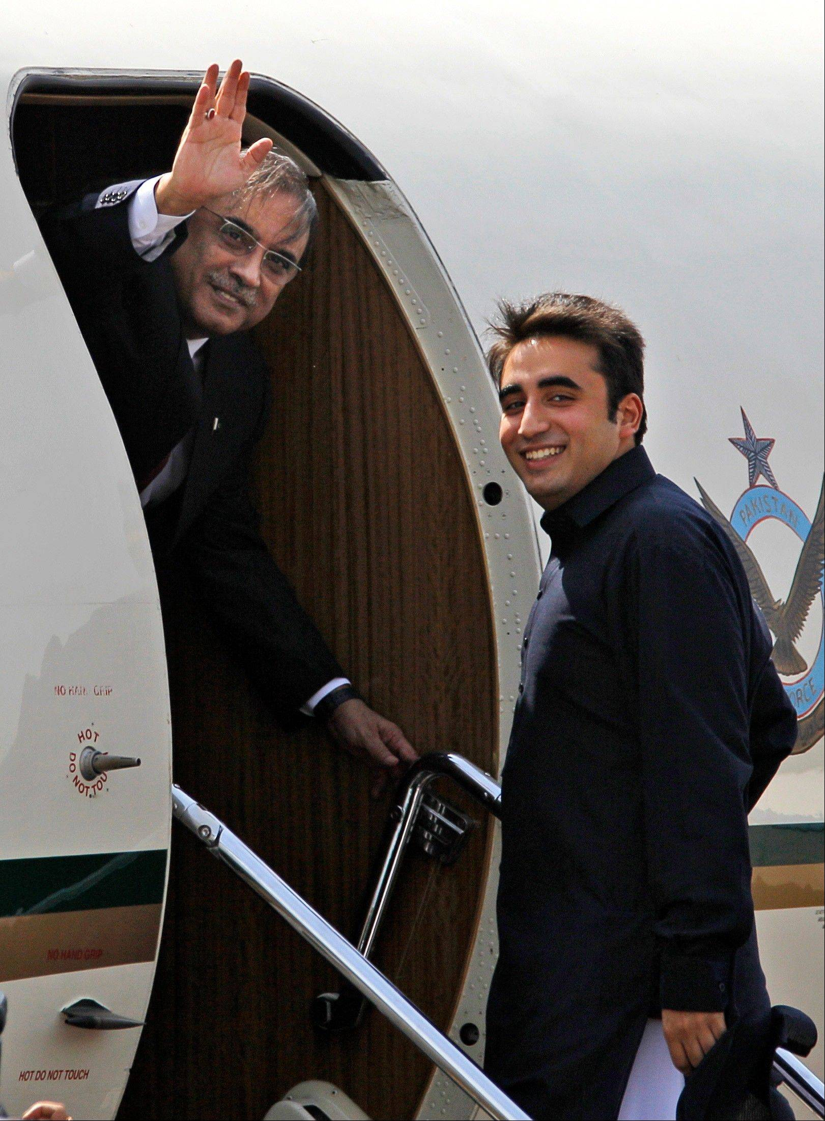In this April 8, 2012 photo, PakistanI President Asif Ali Zardari, left, waves as his son Bilawal Bhutto Zardari looks on while departing for Jaipur at the Palam Airfield in New Delhi, India.