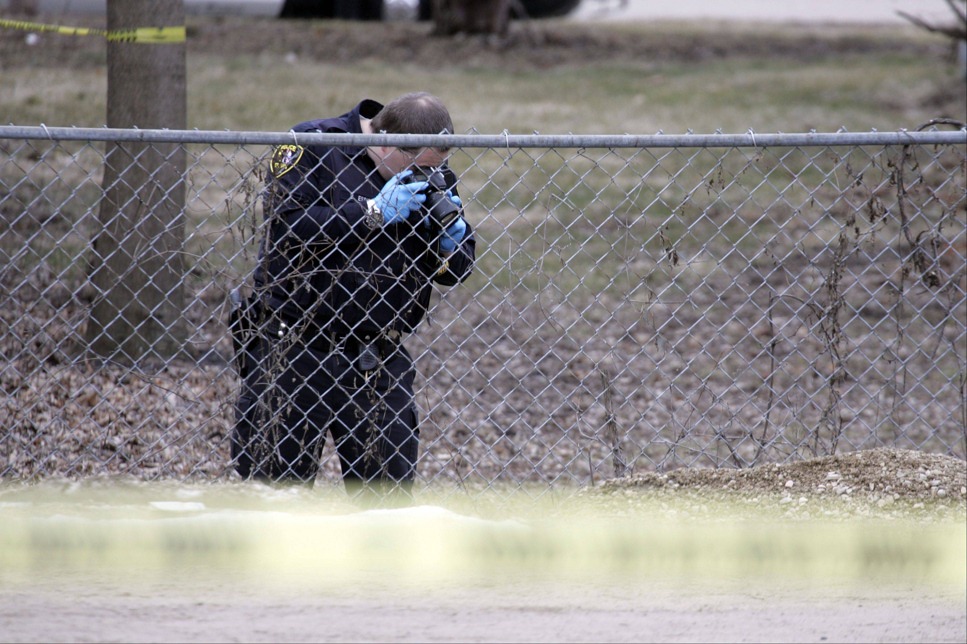 An unidentified Elgin police officer documents the scene Wednesday in the 200 block of Silver Court where a 19-year-old Elgin man was found dead late Tuesday night.