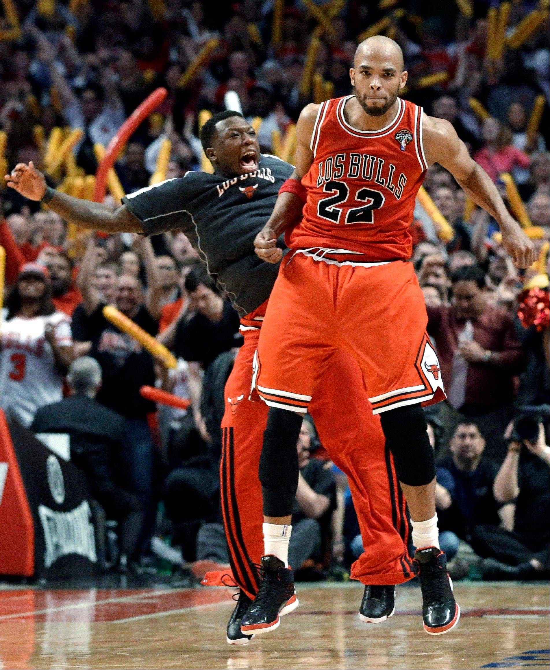 Bulls forward Taj Gibson (22) celebrates with Nate Robinson after scoring a basket during the second half of an NBA basketball game against the Miami Heat in Chicago on Wednesday, March 27, 2013. The Bulls won 101-97, ending the Heat's 27-game winning streak.