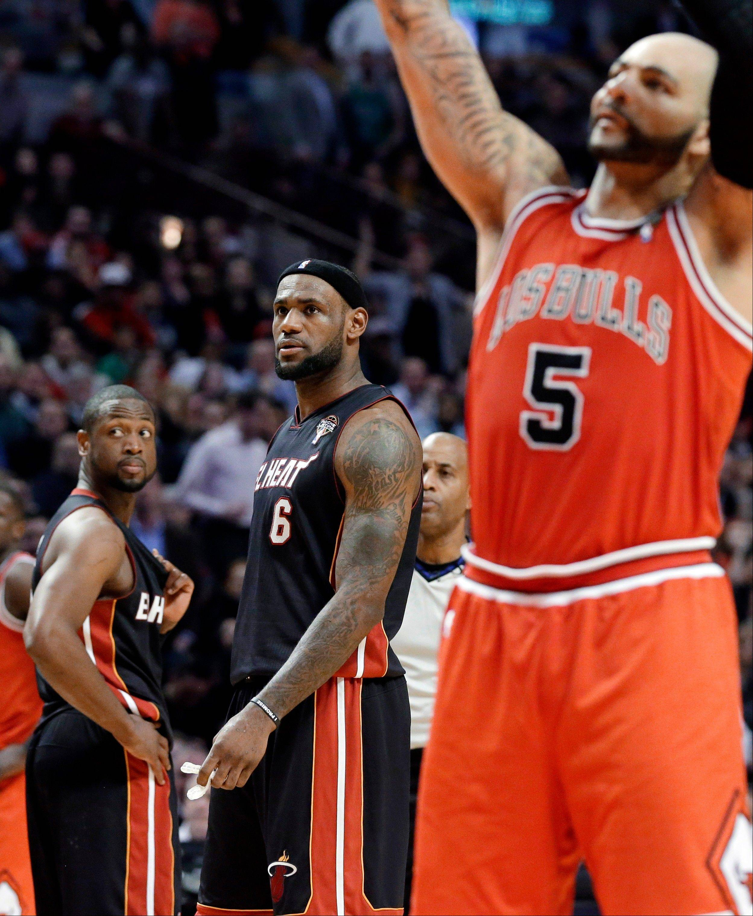 Miami Heat guard Dwyane Wade, left, and forward LeBron James, watch Chicago Bulls forward Carlos Boozer shoot a free throw after James fouled him during the fourth quarter of an NBA basketball game in Chicago on Wednesday, March 27, 2013. The Bulls won 101-97, ending the Heat's 27-game winning streak.