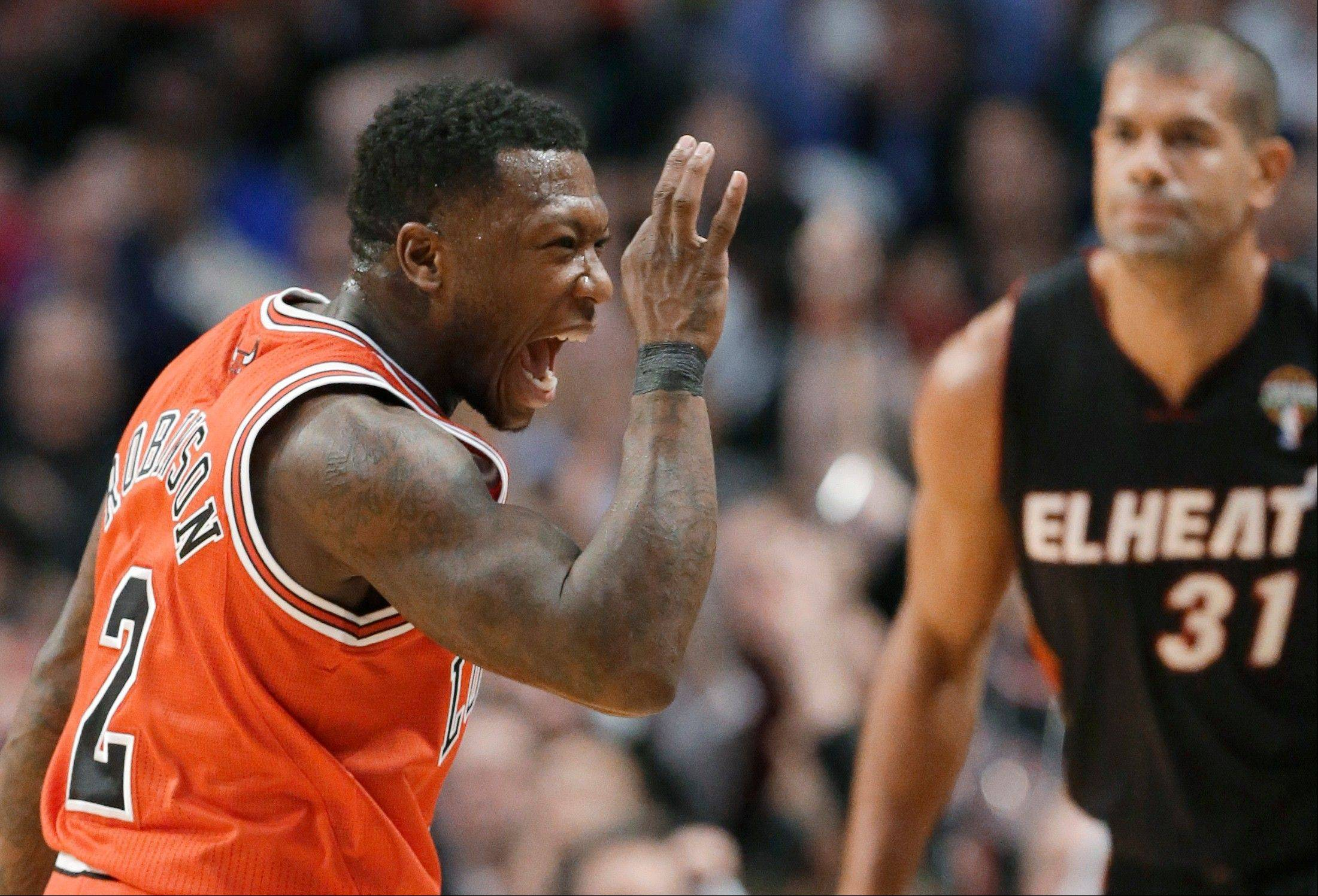 Chicago Bulls guard Nate Robinson, left, celebrates a 3-point shot, as Miami Heat forward Shane Battier watches Wednesday night at the United Center.