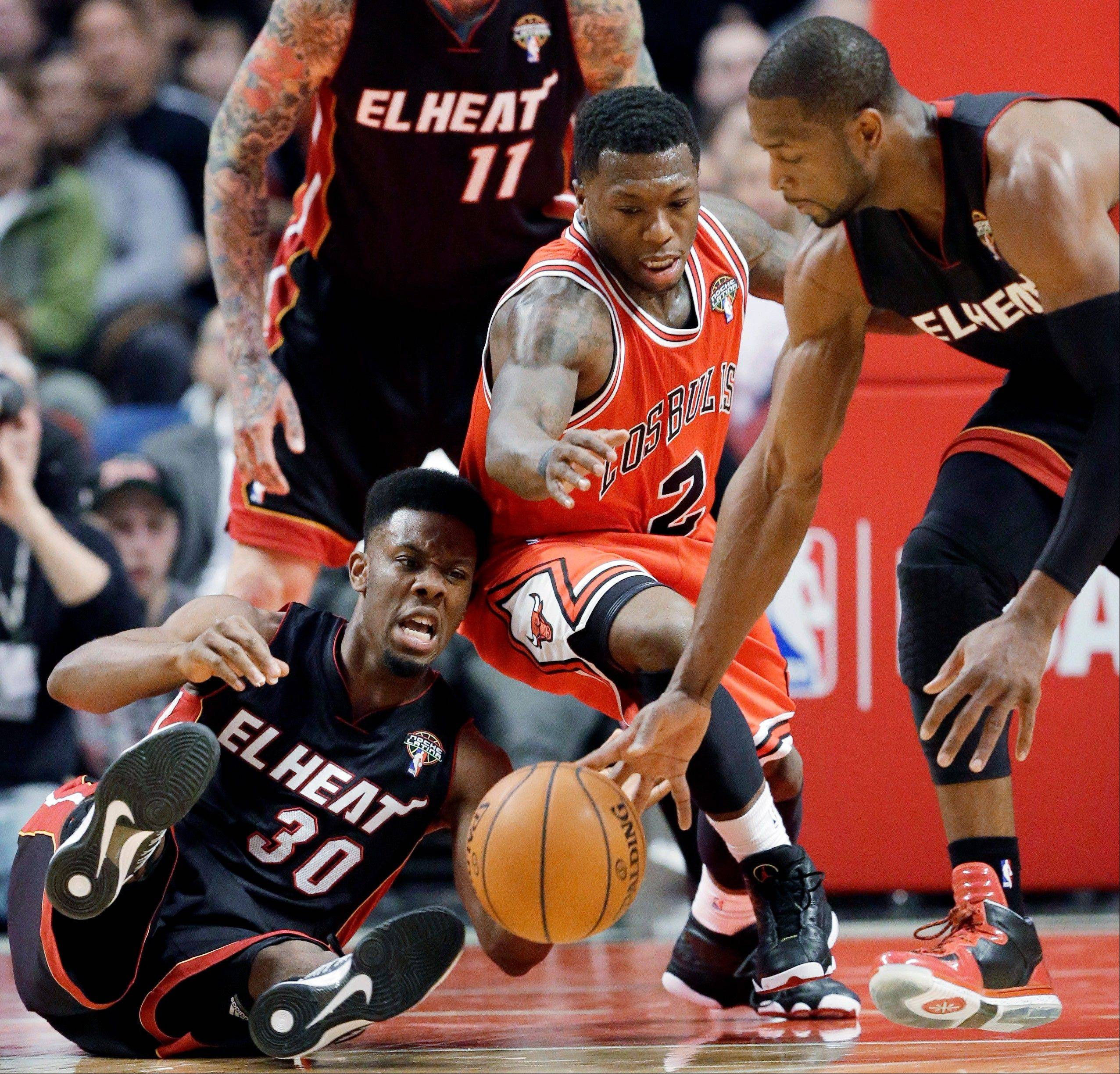 Miami Heat guards Norris Cole (30) and Dwyane Wade, right, scramble for a loose ball against Chicago Bulls guard Nate Robinson Wednesday night at the United Center.