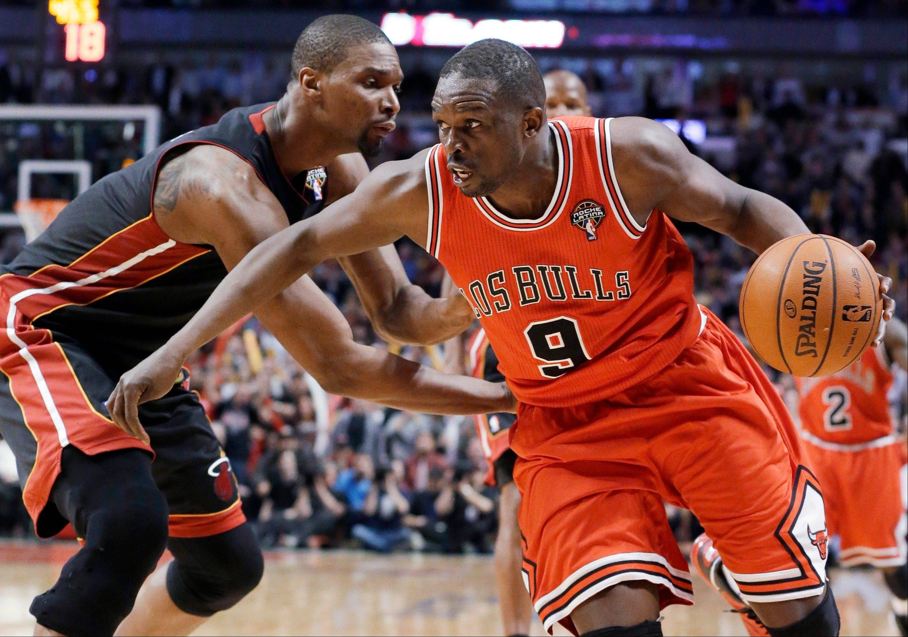 Chicago Bulls forward Luol Deng, right, drives against Miami Heat center Chris Bosh Wednesday night at the United Center. The Bulls won 101-97, ending the Heat's 27-game winning streak.