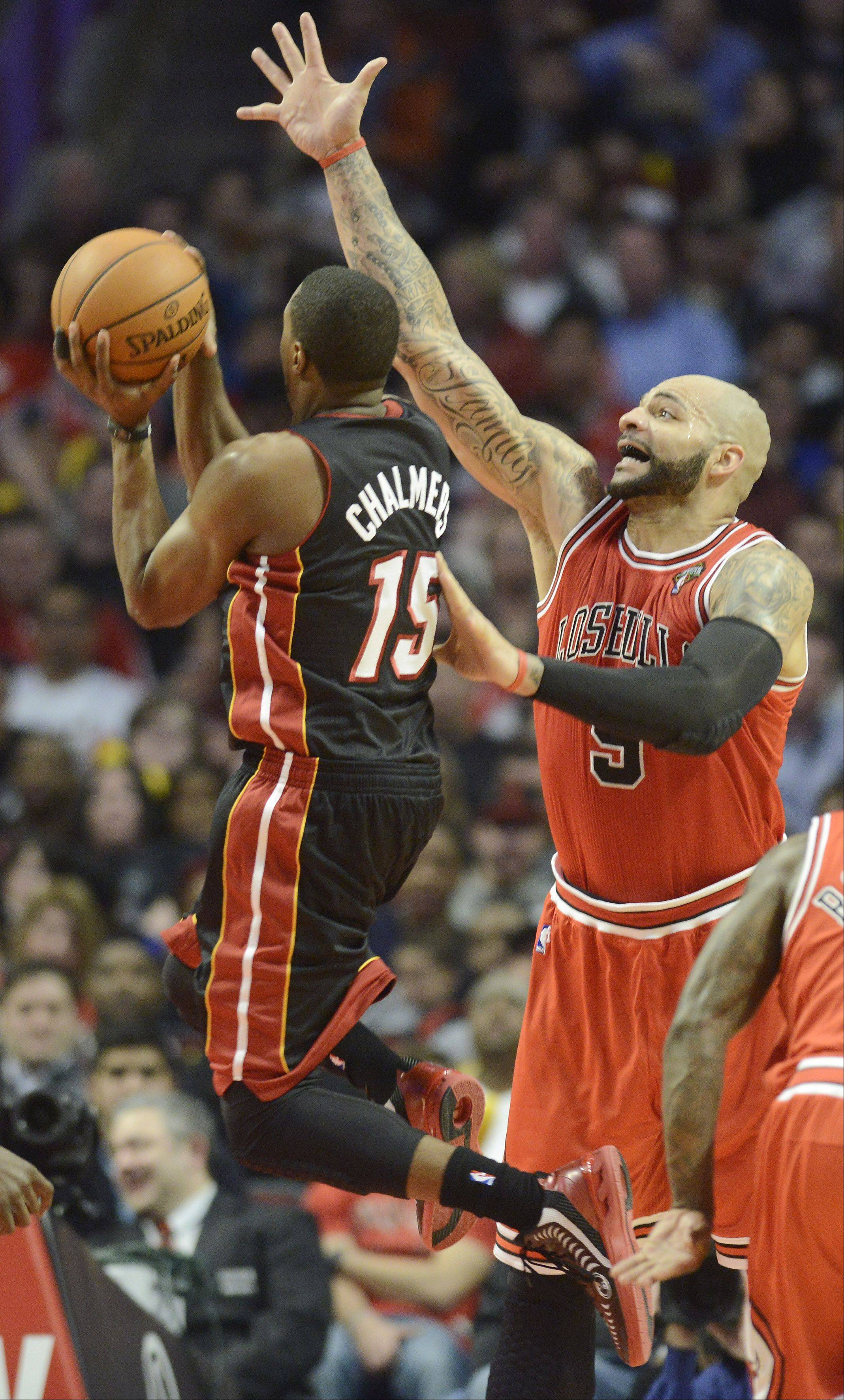 JOE LEWNARD/jlewnard@dailyherald.comCarlos Boozer of the Bulls defends a shot by Mario Chalmers of the Miami Heat.