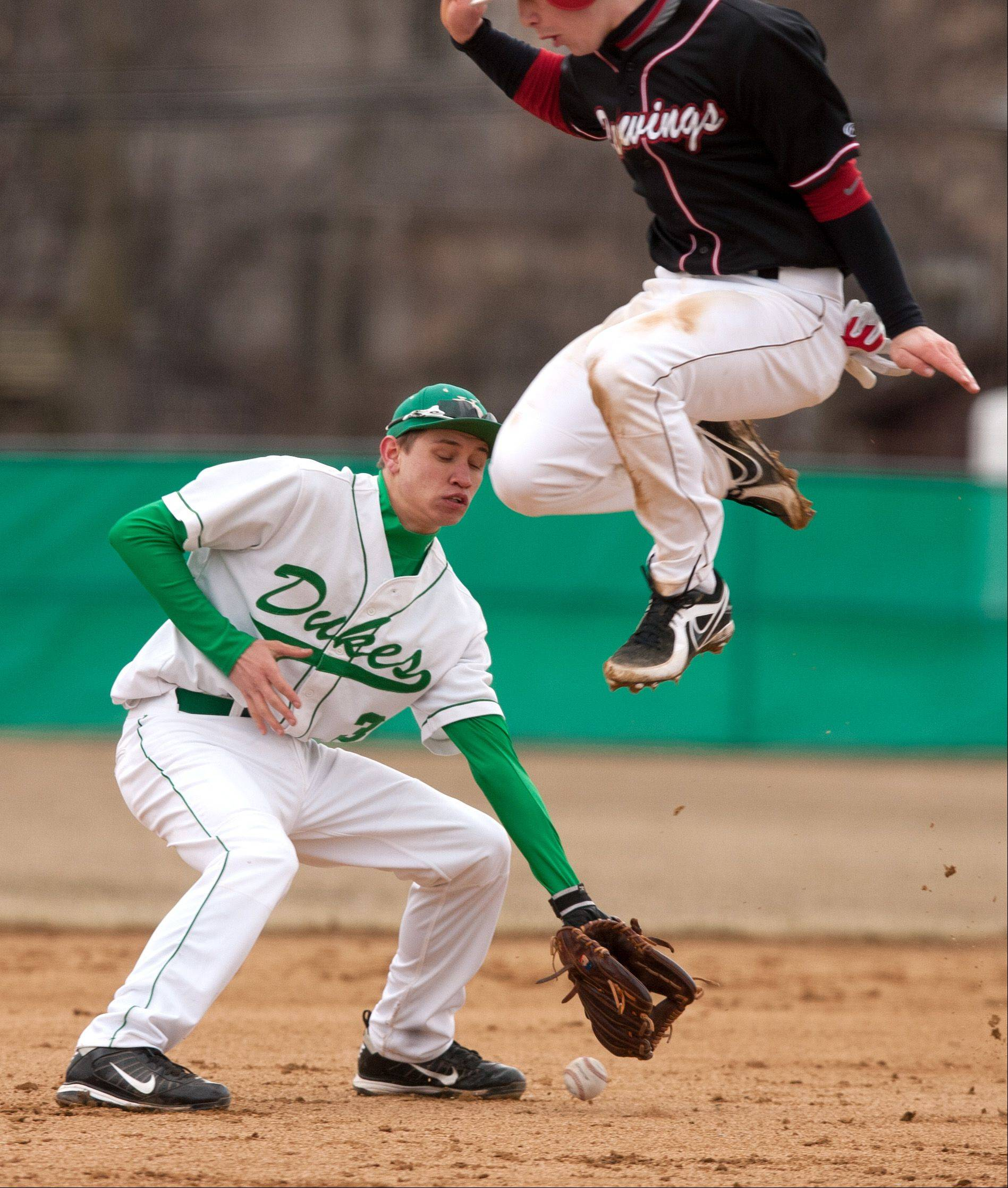 Benet baserunner Joe Boyle jumps to avoid getting hit by the ball, as York's Tyler Zunkel looks to field the ball, during baseball action in Elmhurst.