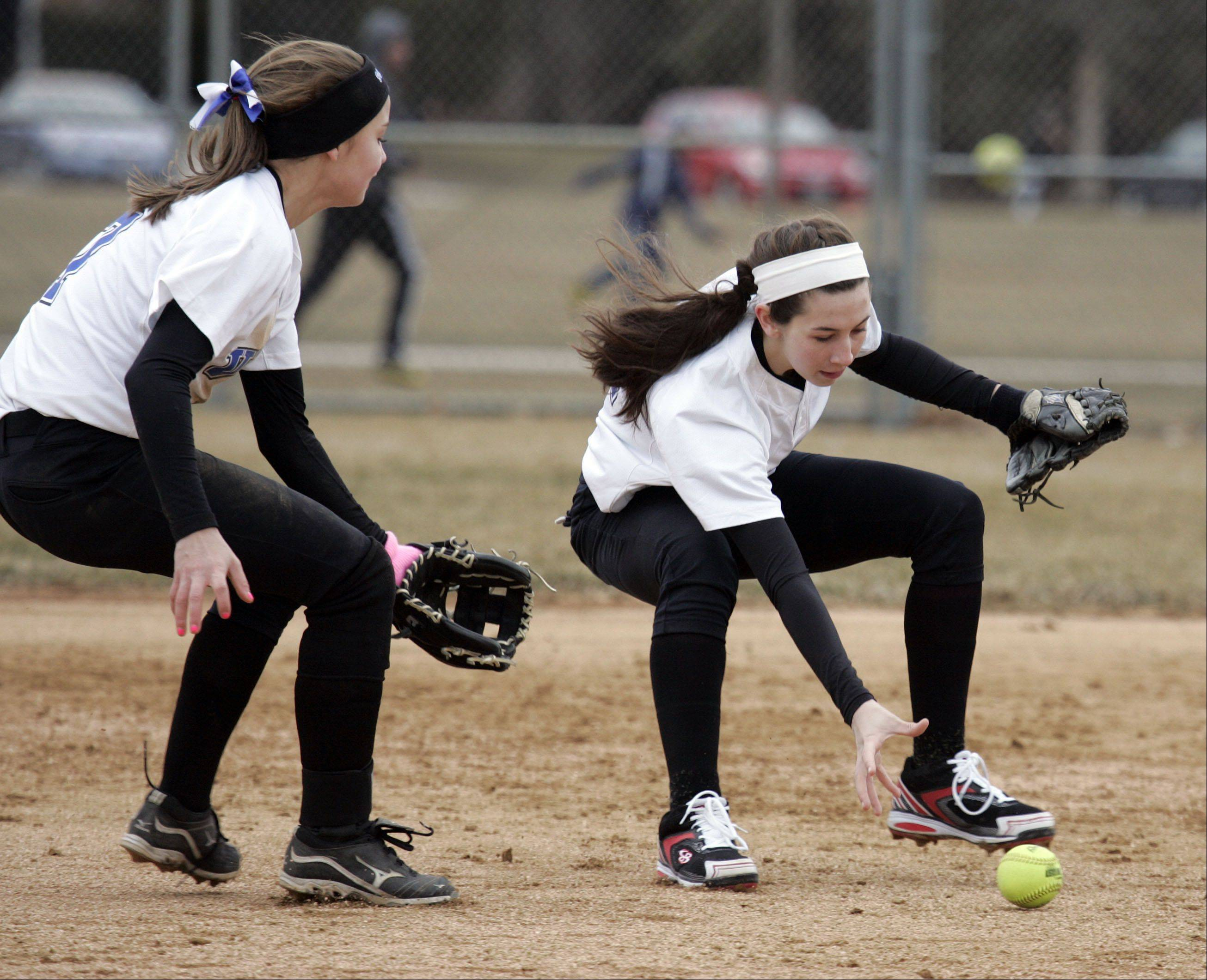 Geneva's Anna Geary, 7, and Alexis Garibay, 17, make a play for a ground ball during Oswego at Geneva softball Wednesday.