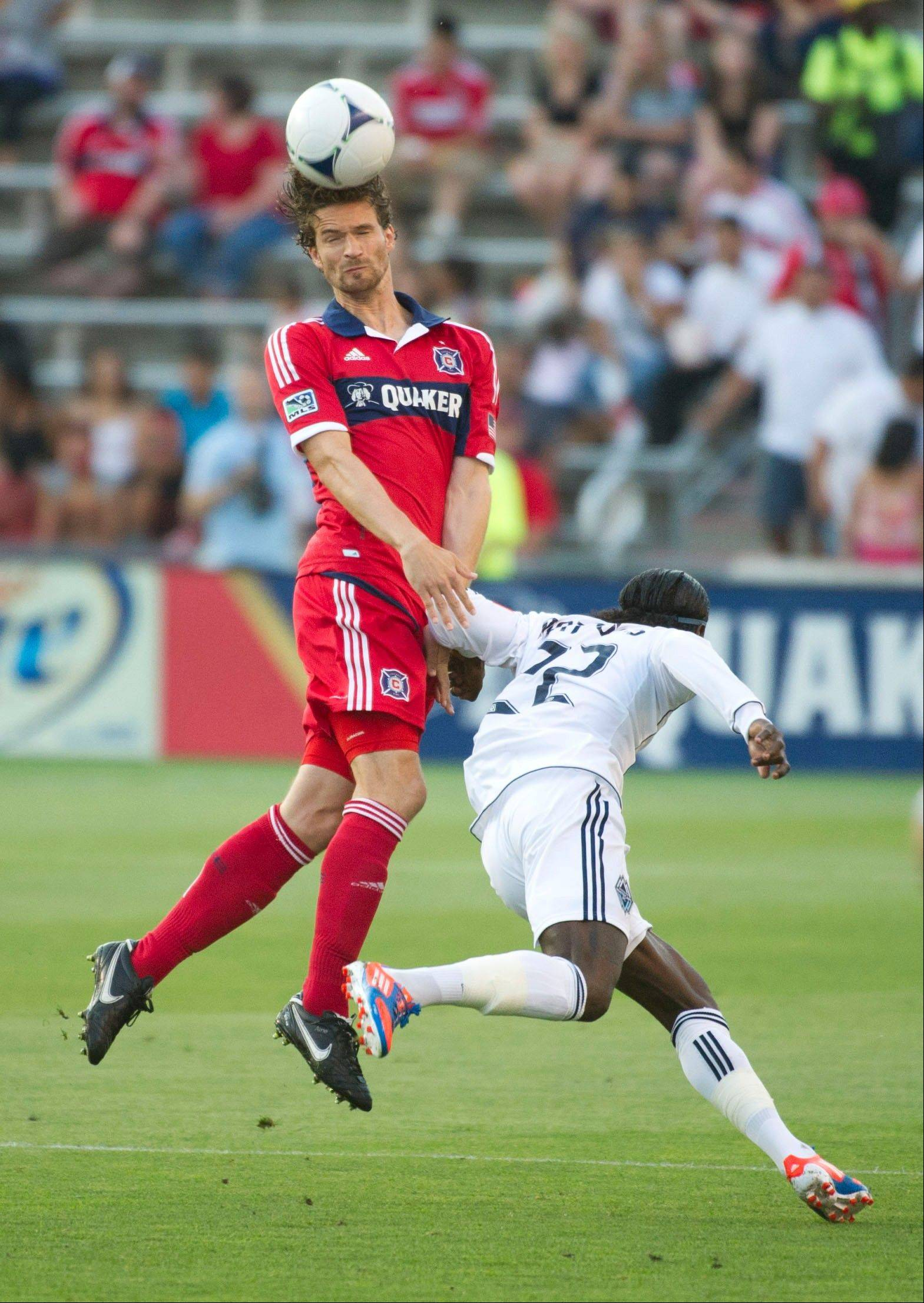 Chicago Fire defender Arne Friedrich, left, and Vancouver Whitecaps FC forward Darren Mattocks go for the ball during the first half an MLS soccer game July 14, 2012, at Toyota Park in Bridgeview.