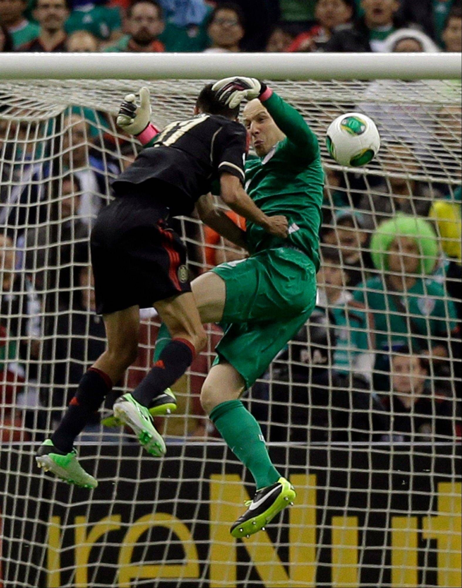 Mexico's Jesus Zabala, left, collides with United States goalkeeper Brad Guzan while trying to score during a 2014 World Cup qualifying match Tuesday at the Aztec stadium in Mexico City.
