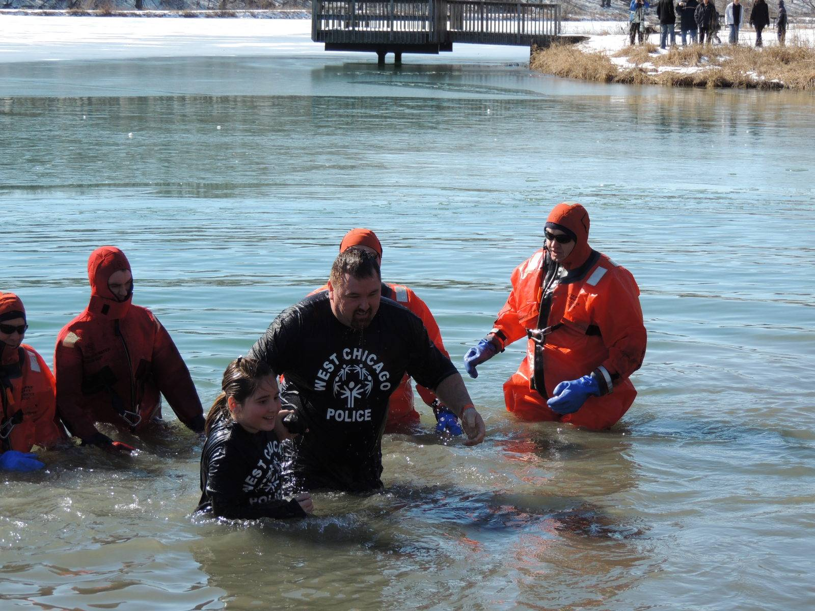 Exiting the cold water of Loon Lake in Silver Springs State Park, West Chicago Police Detective Robbi Peterson and his 9-year old daughter Taylor are all smiles as they complete the challenge of the Polar Plunge for Special Olympics Illinois and raise $600 to donate to the organization.