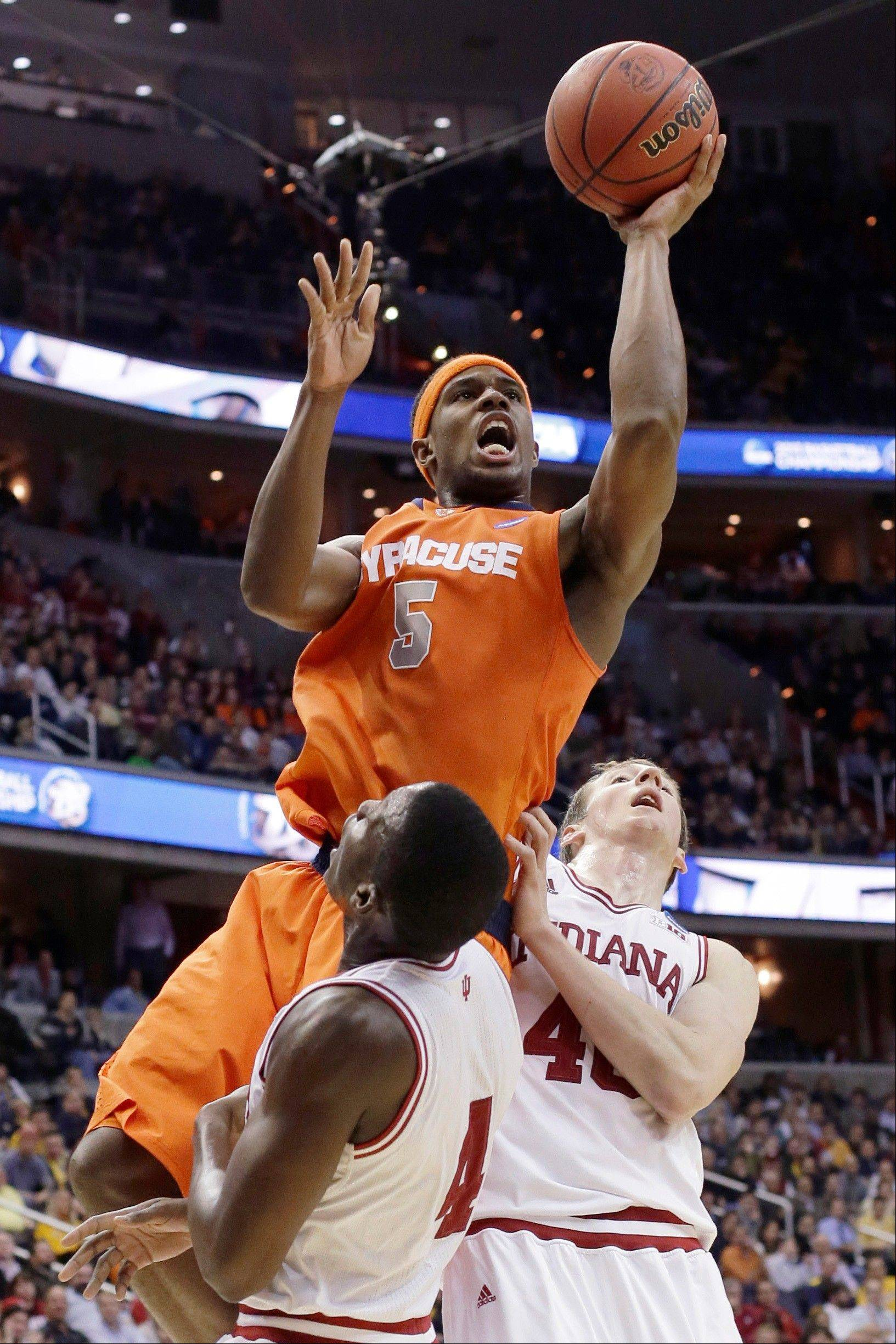 Syracuse forward C.J. Fair (5) shoots over Indiana guard Victor Oladipo (4) and forward Cody Zeller (40) during the second half of an East Regional semifinal in the NCAA men's college basketball tournament, Thursday, March 28, 2013, in Washington. (AP Photo/Pablo Martinez Monsivais)