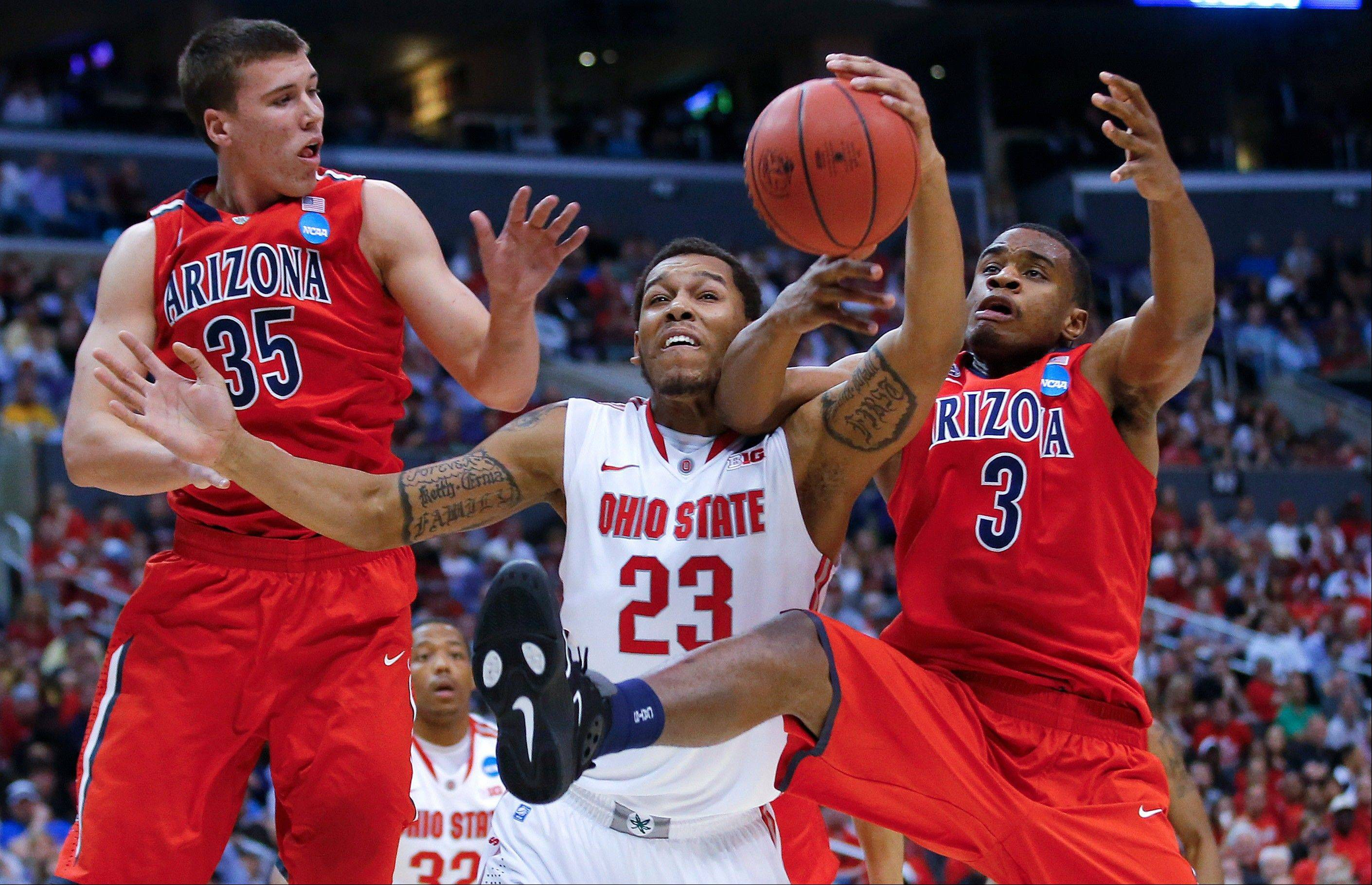 Ohio State's Amir Williams, center, is double-teamed by Arizona's Kaleb Tarczewski, left, and Kevin Parrom during the first half of a West Regional semifinal in the NCAA men's college basketball tournament, Thursday, March 28, 2013, in Los Angeles. (AP Photo/Jae C. Hong)