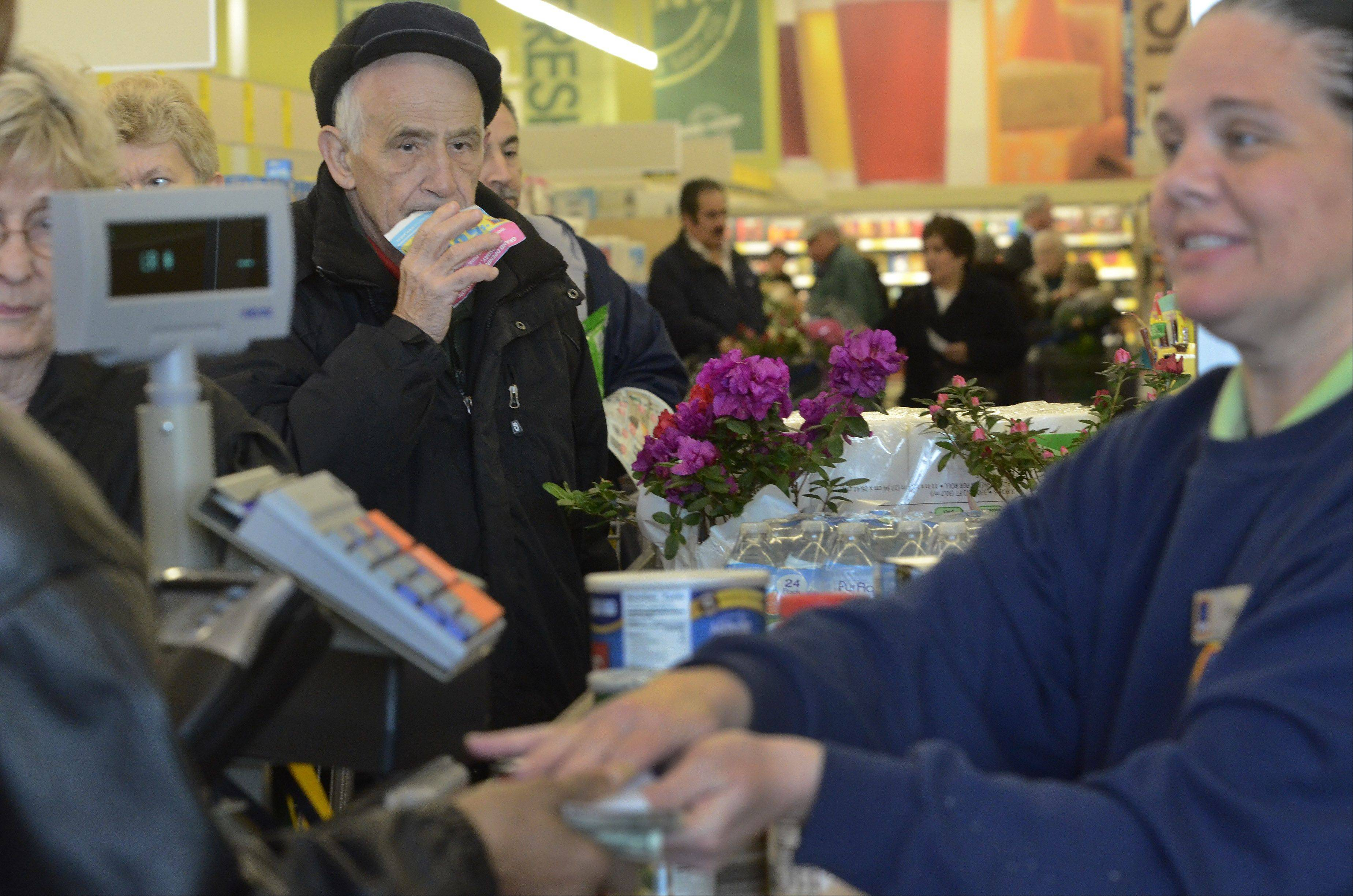 Joe Klett of Mount Prospect waits in line with his coupon as Aldi cashier Kim Buchen gives change to a customer as the new Aldi grocery store formally opens Thursday in Mount Prospect.