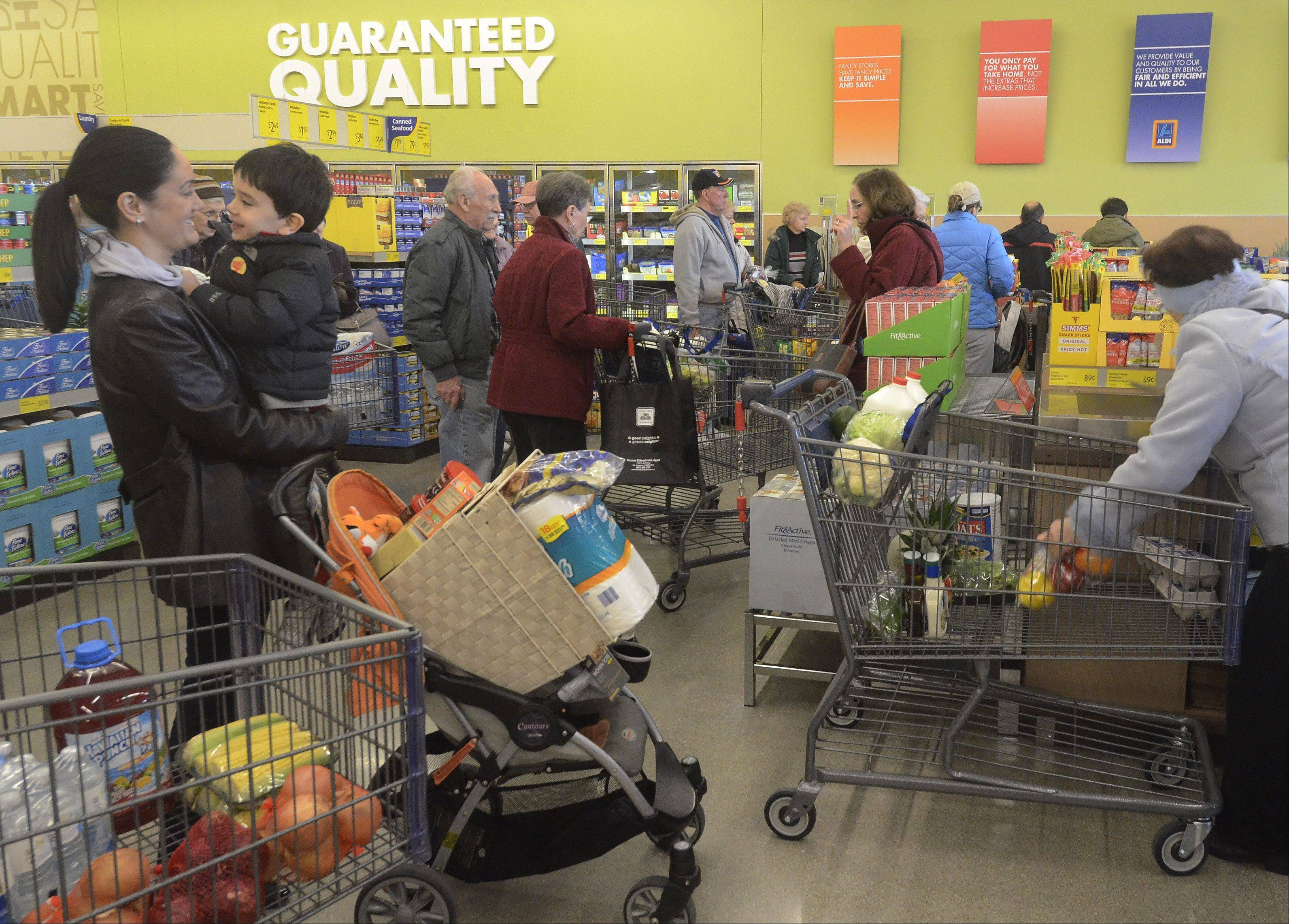 Irene and Panos Makropoulos wait in line to check out Thursday at the new Aldi grocery store in Mount Prospect.